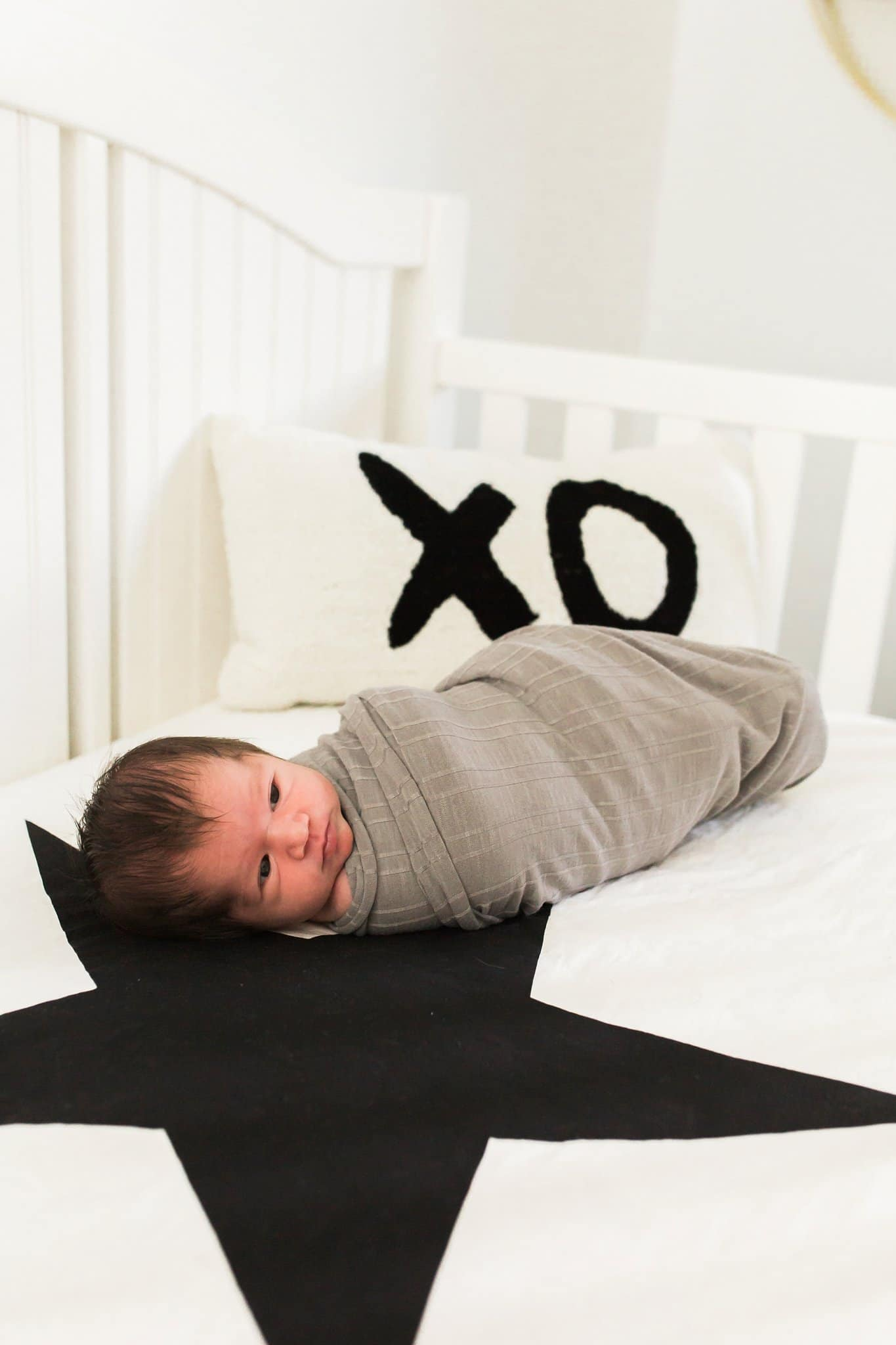 Newborn in crib with pottery barn pillows