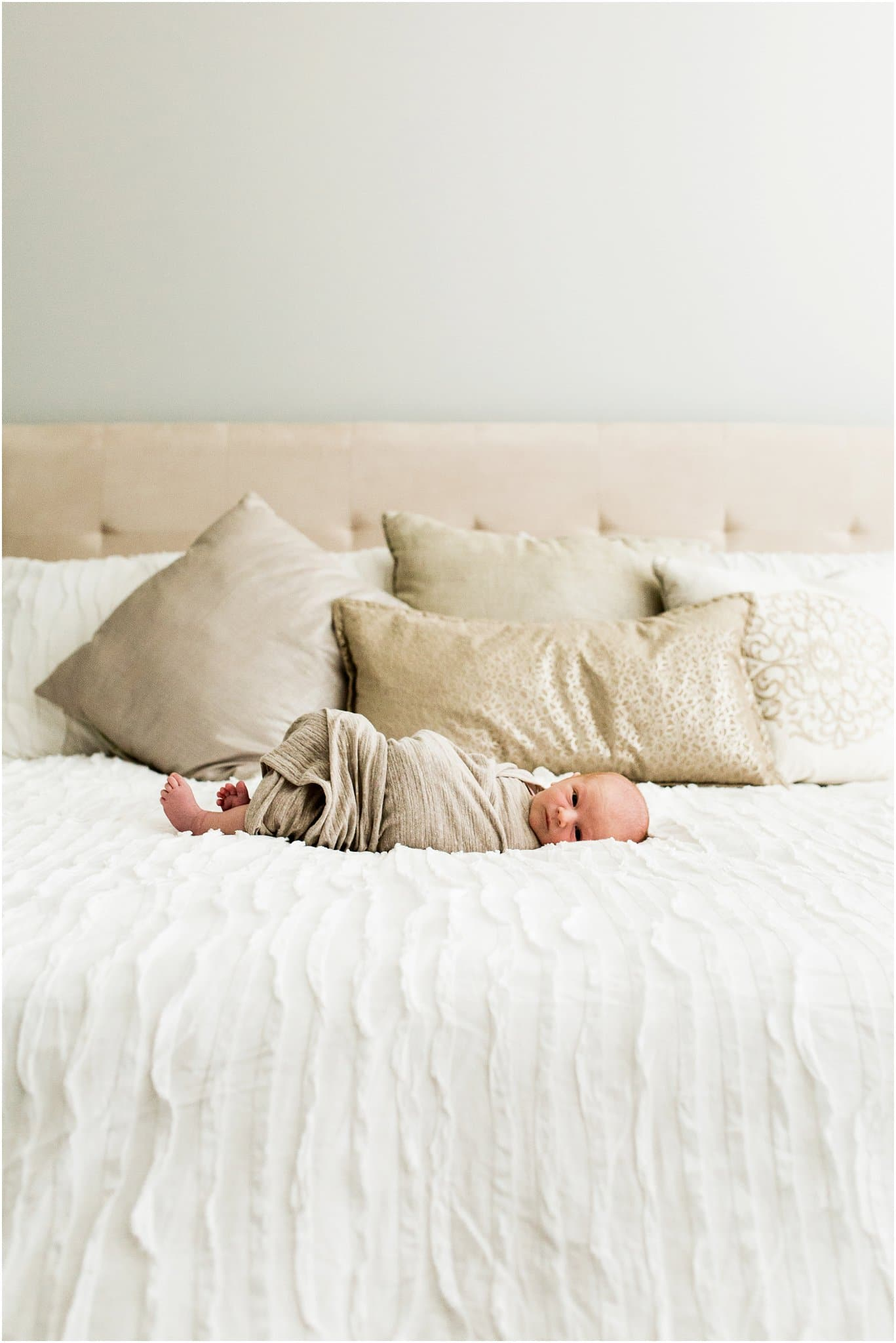 newborn boy swaddled on bed