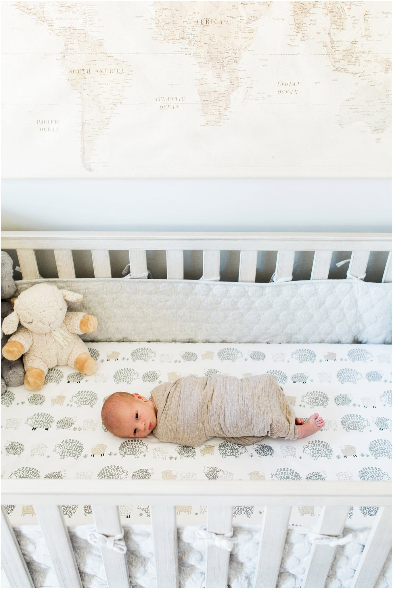 newborn boy in neutral crib with world map decor