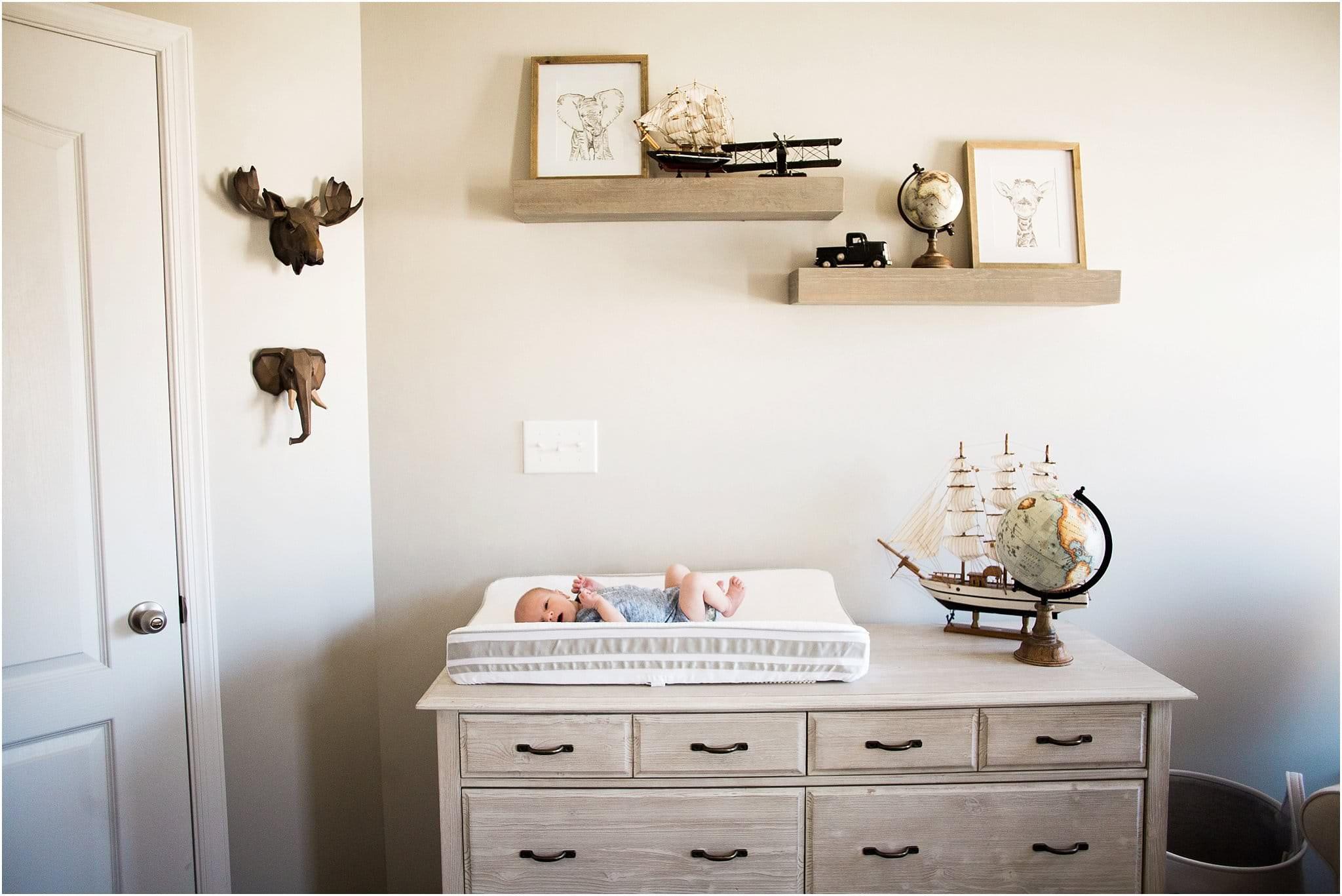 newborn boy in nursery with world travel decor