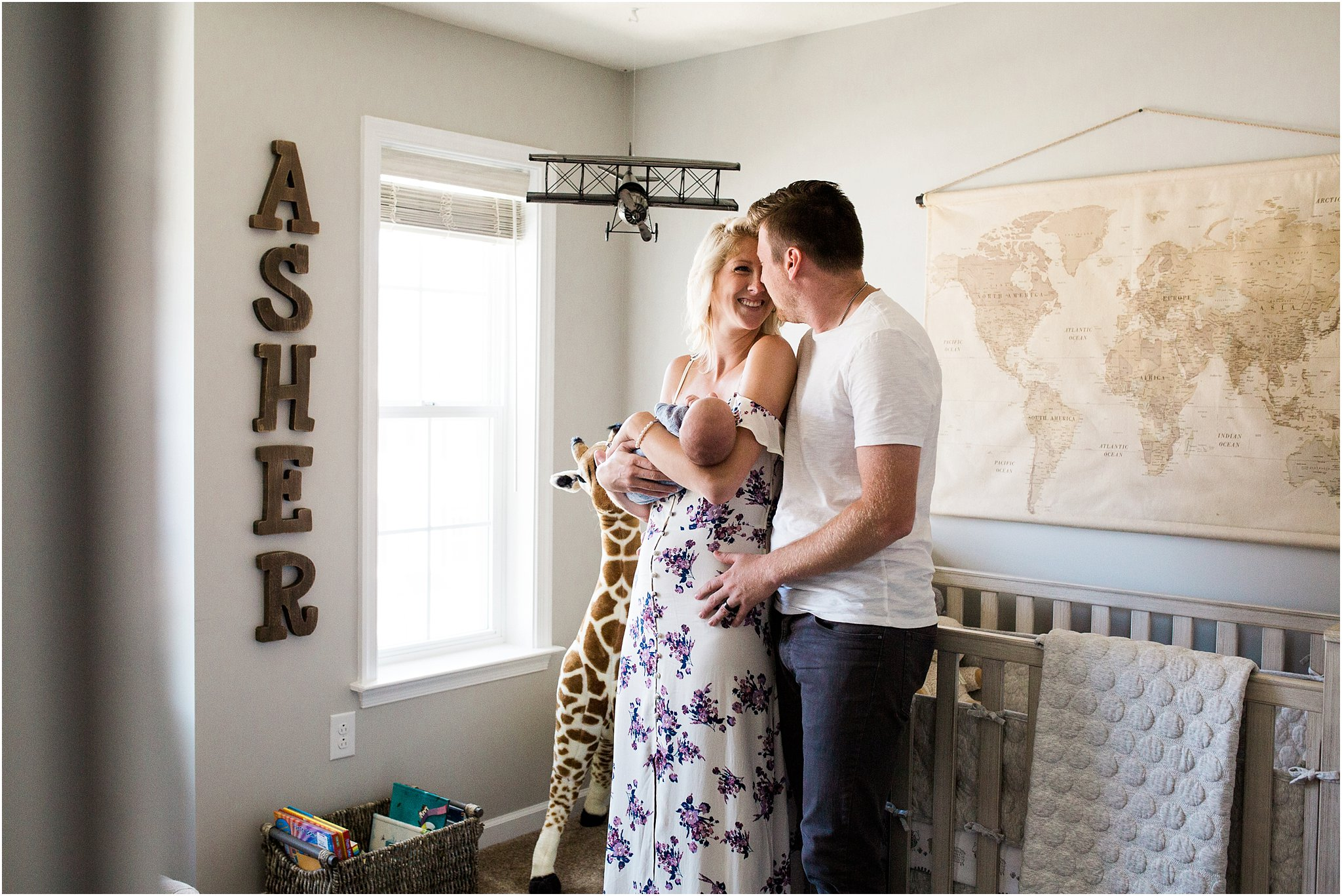 mother and father looking to newborn baby boy in travel inspired home nursery