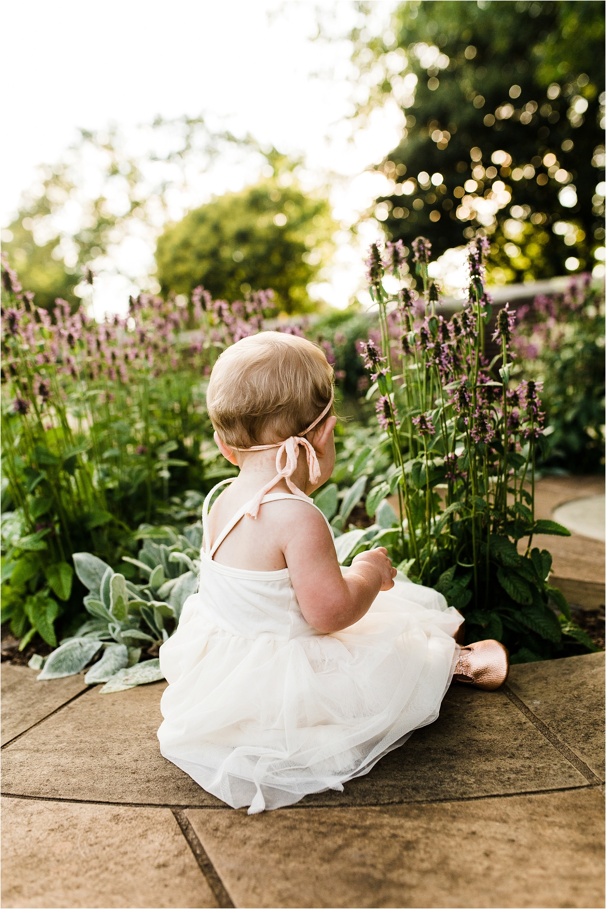 one year old baby girl picking flowers