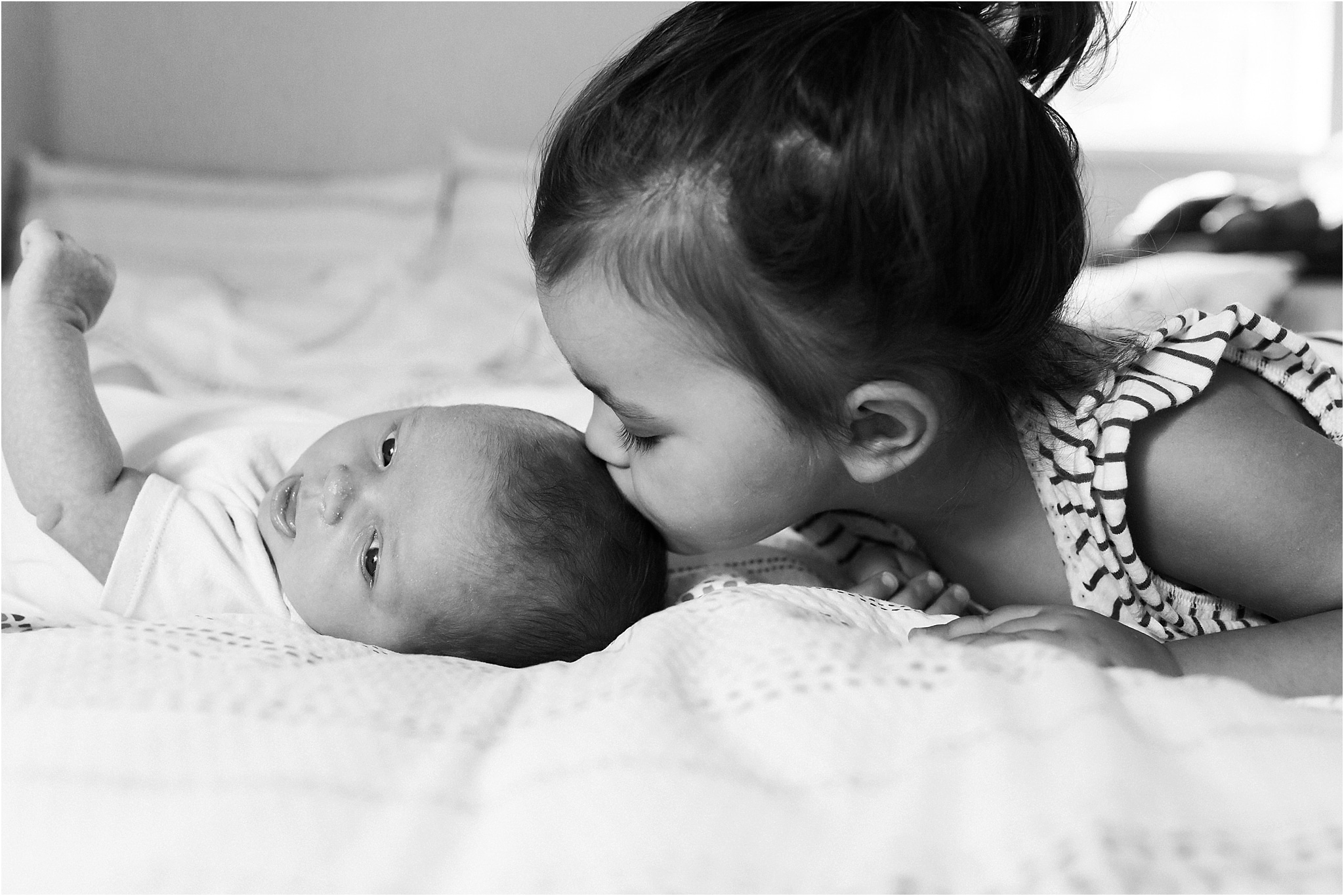 newborn gets sweet kiss from big sister