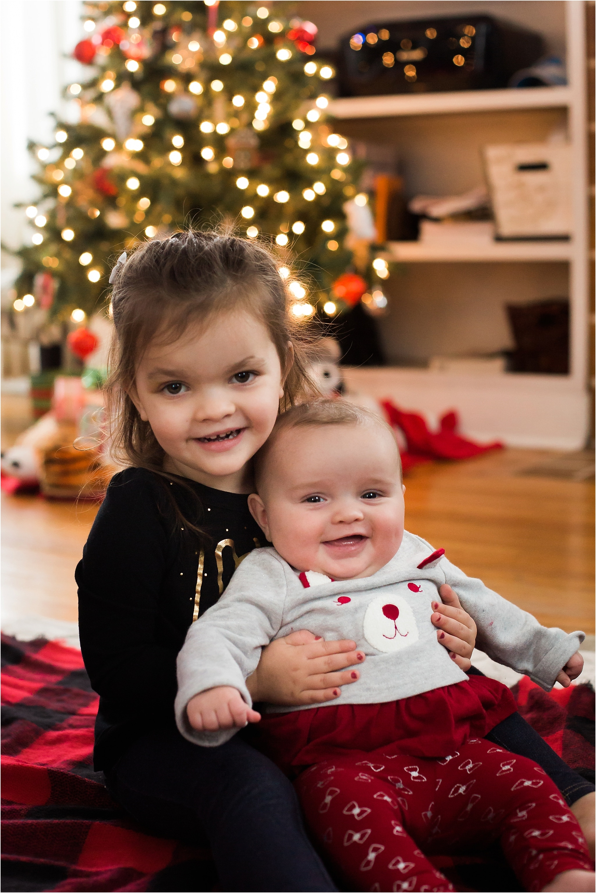 photo of 5 months old girl and toddler sister in front of Christmas tree