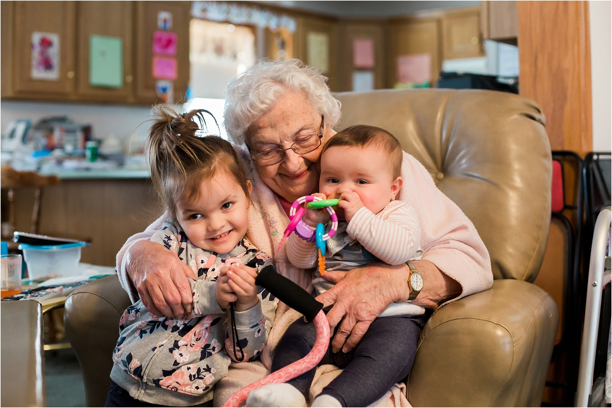 toddler and baby sister snuggling with grandma