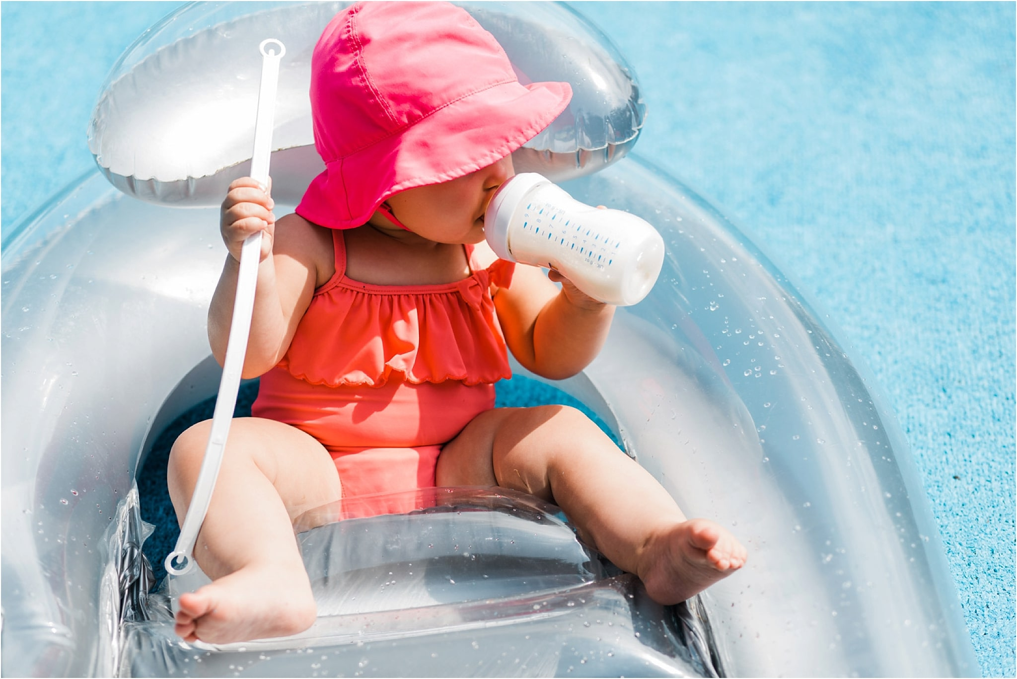 10 month old girl having a bottle at pool