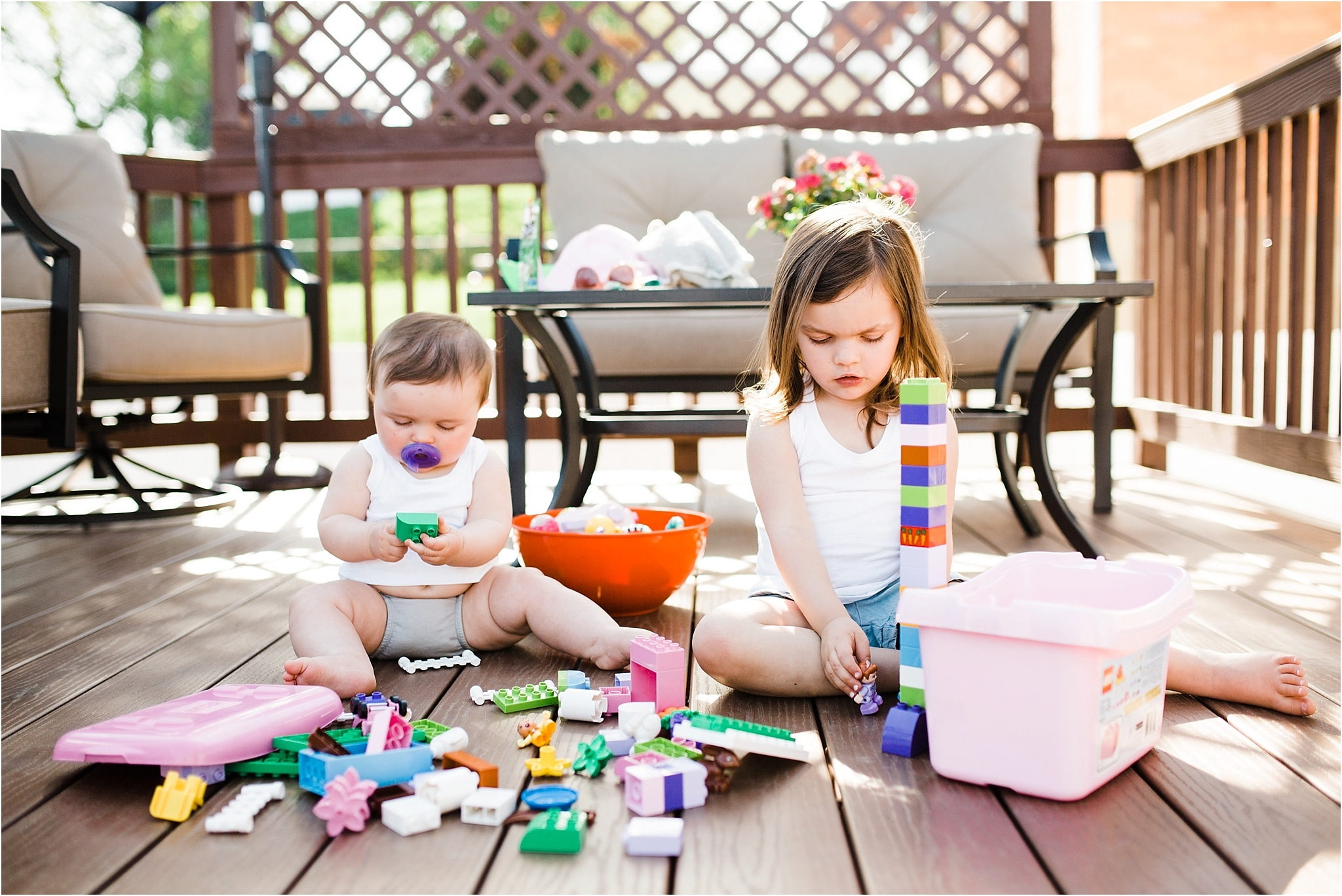 sibling sister playing blocks outdoors together