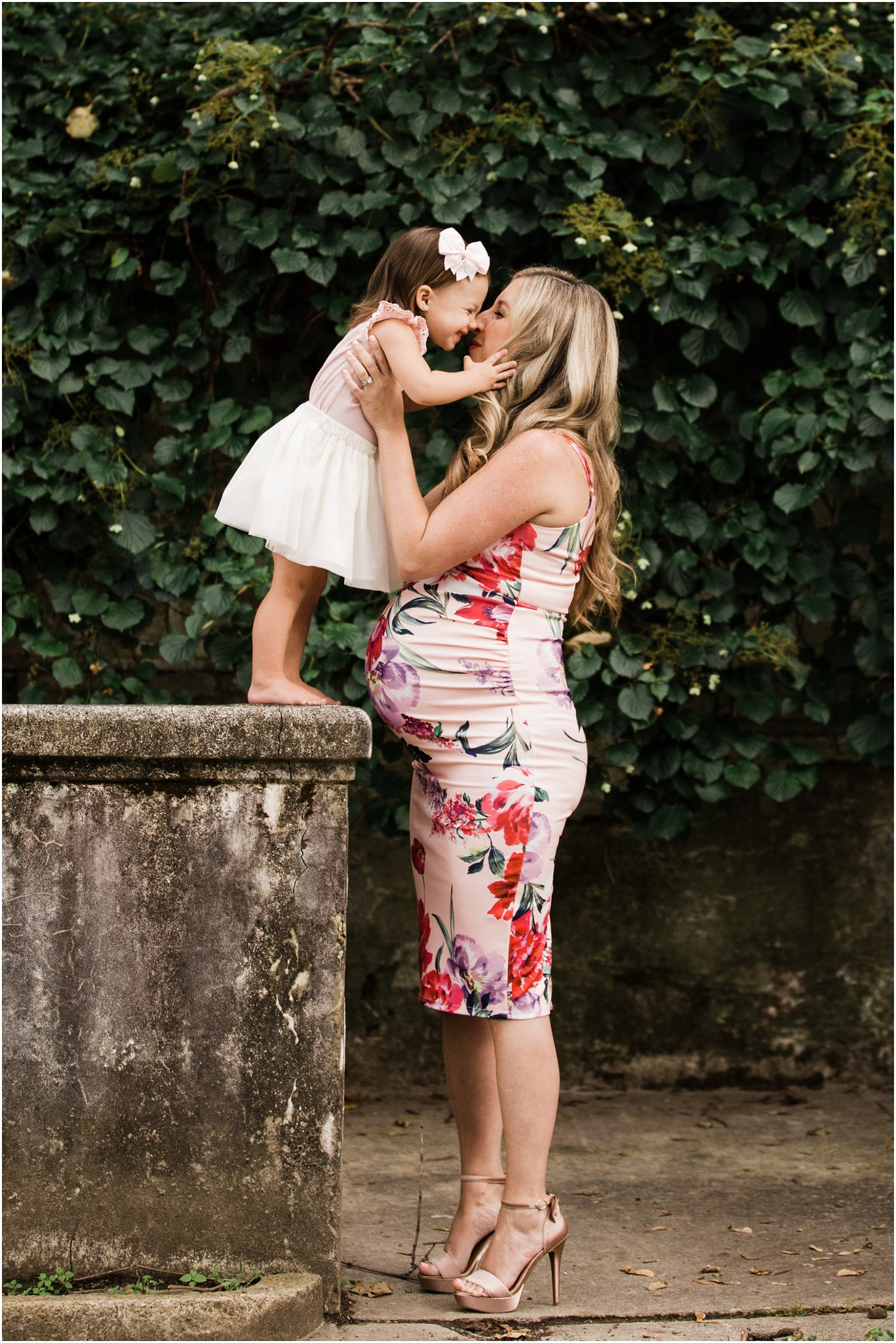 first child kissing expecting mother