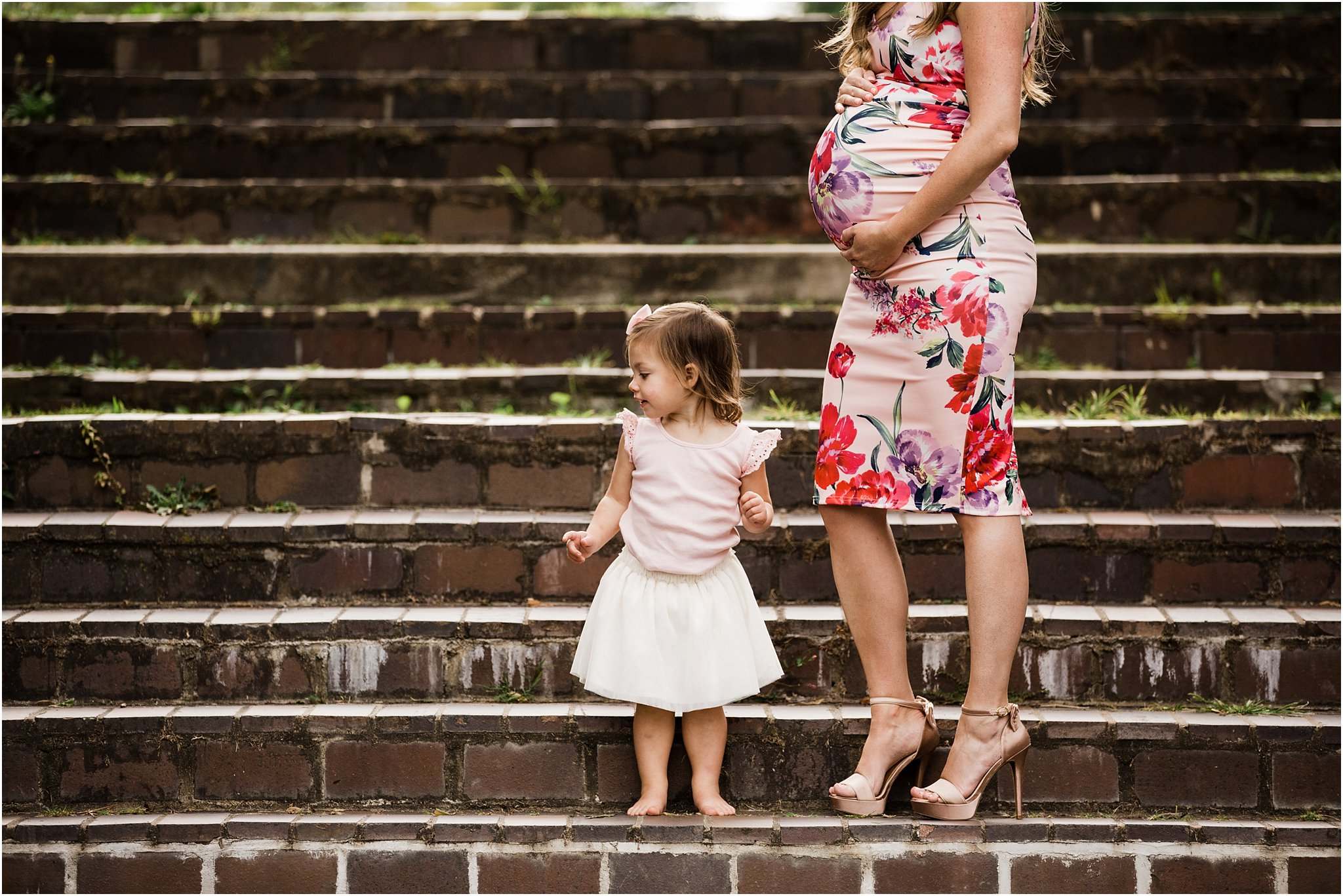 expecting mother in floral dress with toddler daughter