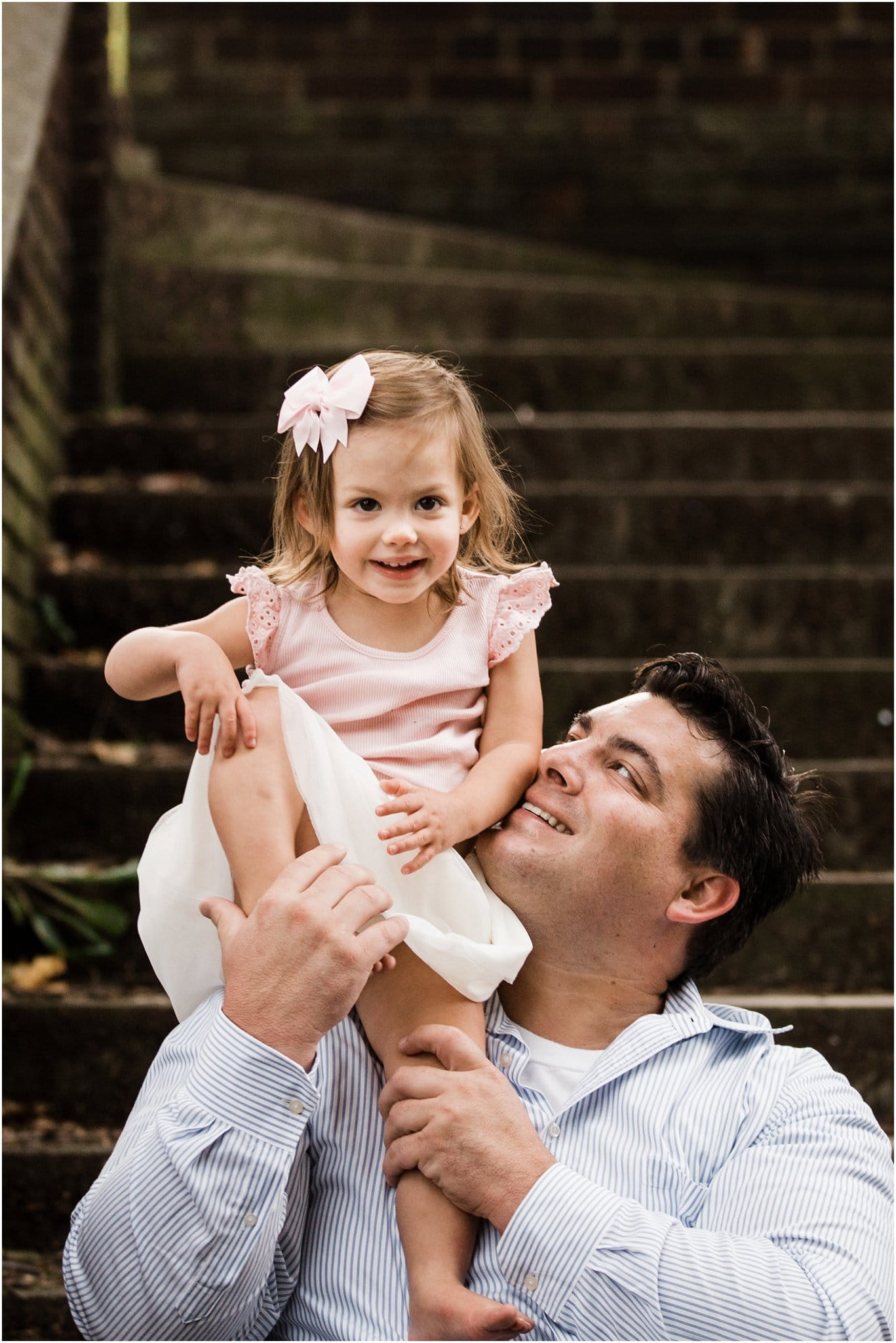 father holding smiling daughter on steps