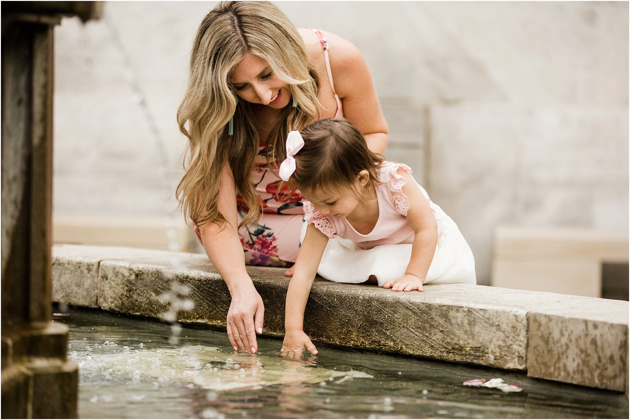 expecting mother and daughter playing in a fountain