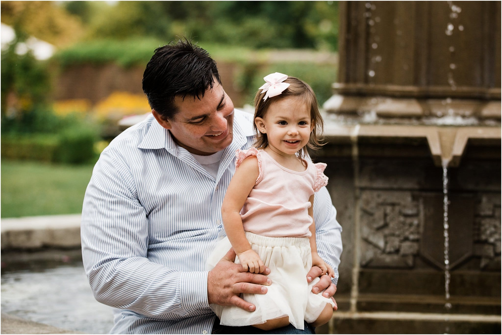 father holding smiling daughter by fountain