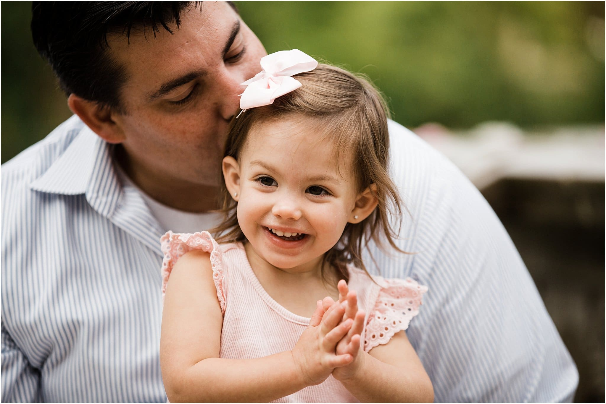father kissing smiling daughter