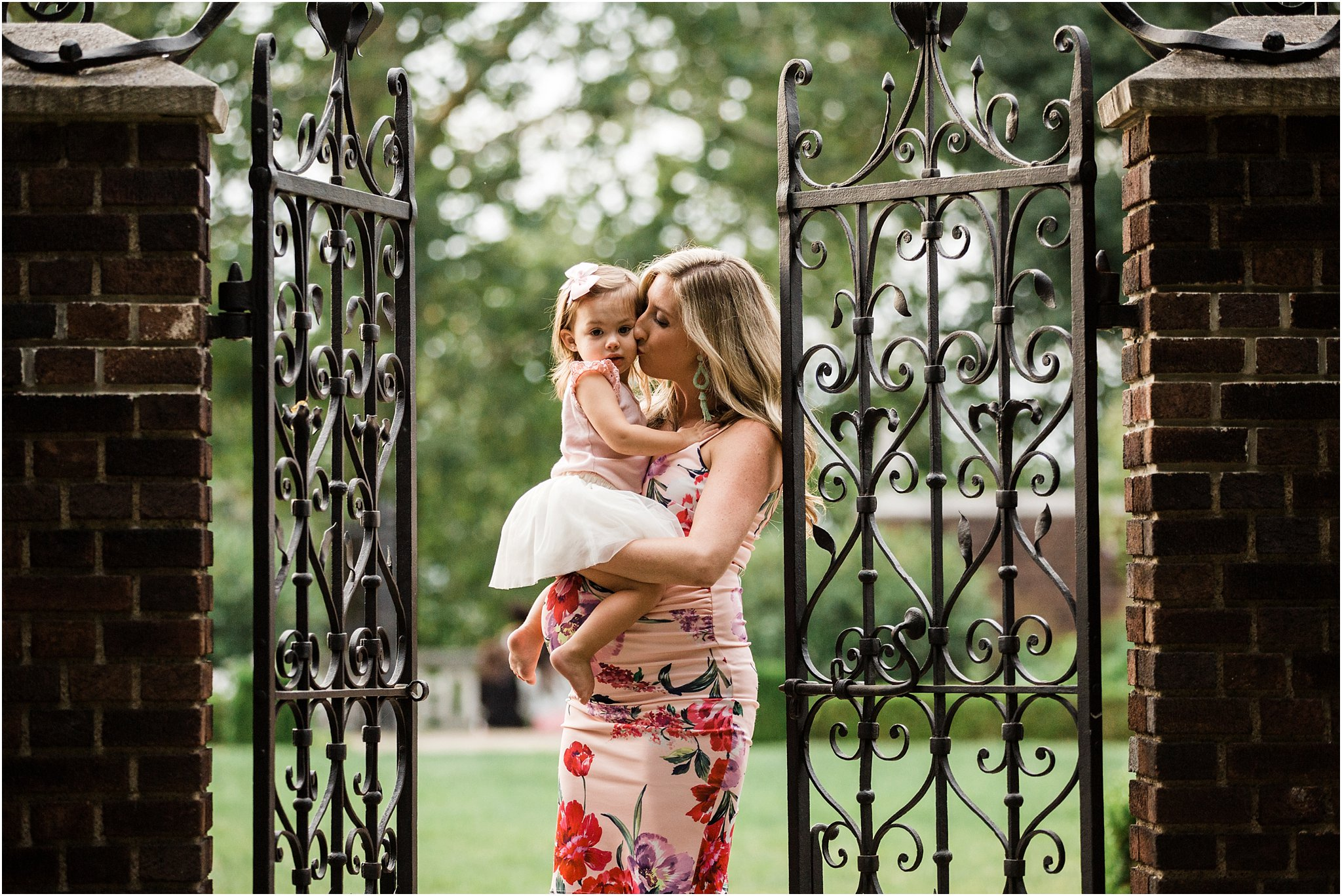 expecting mother holding daughter in iron gate opening