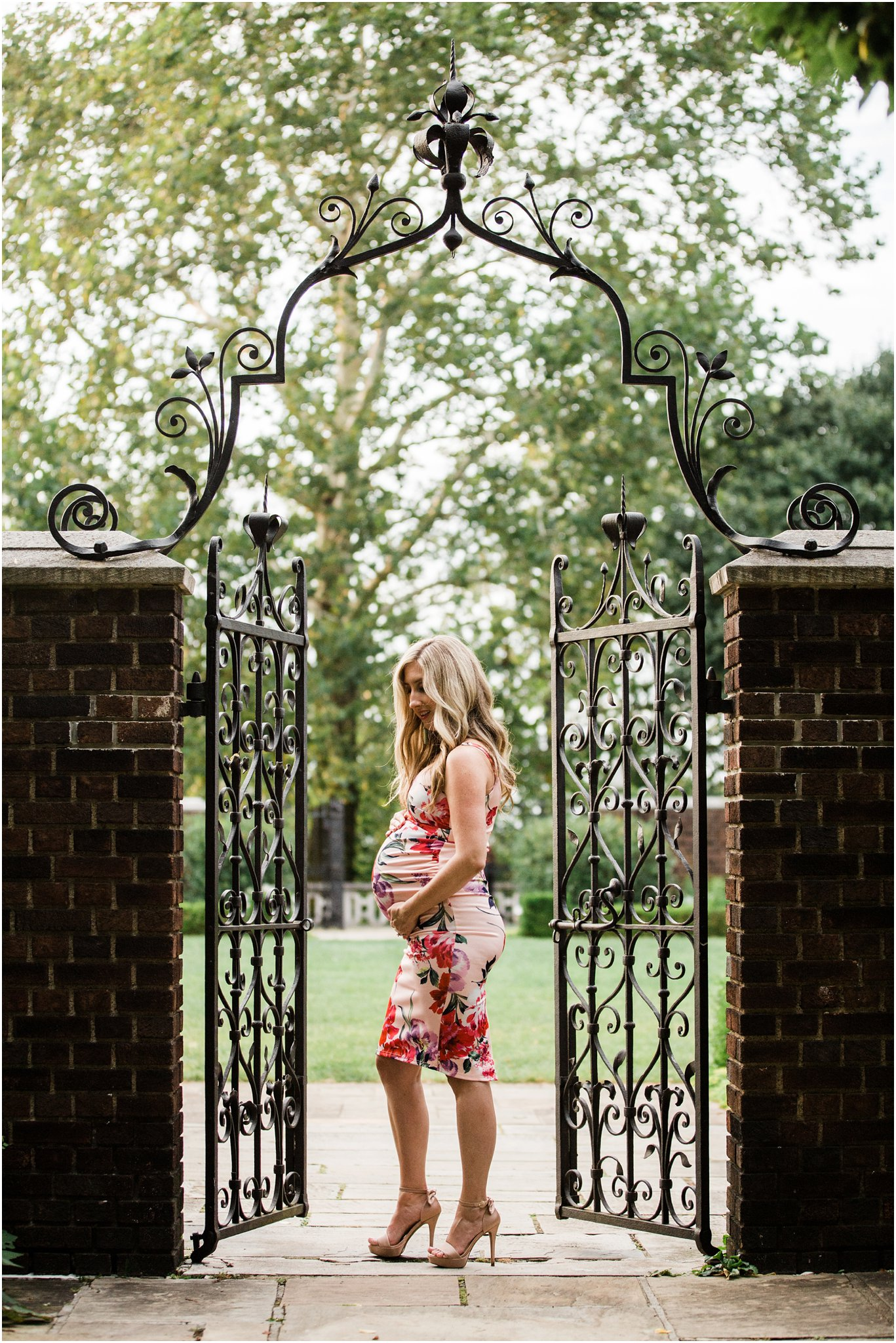 gorgeous mother in form fitting ASOS floral maternity dress between gates at walled garden