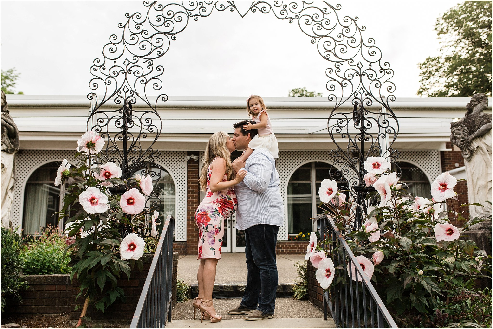 family maternity photos in floral arch