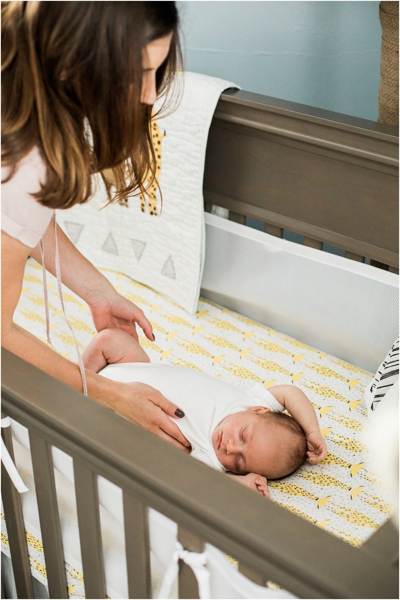 mother putting sleeping baby into crib
