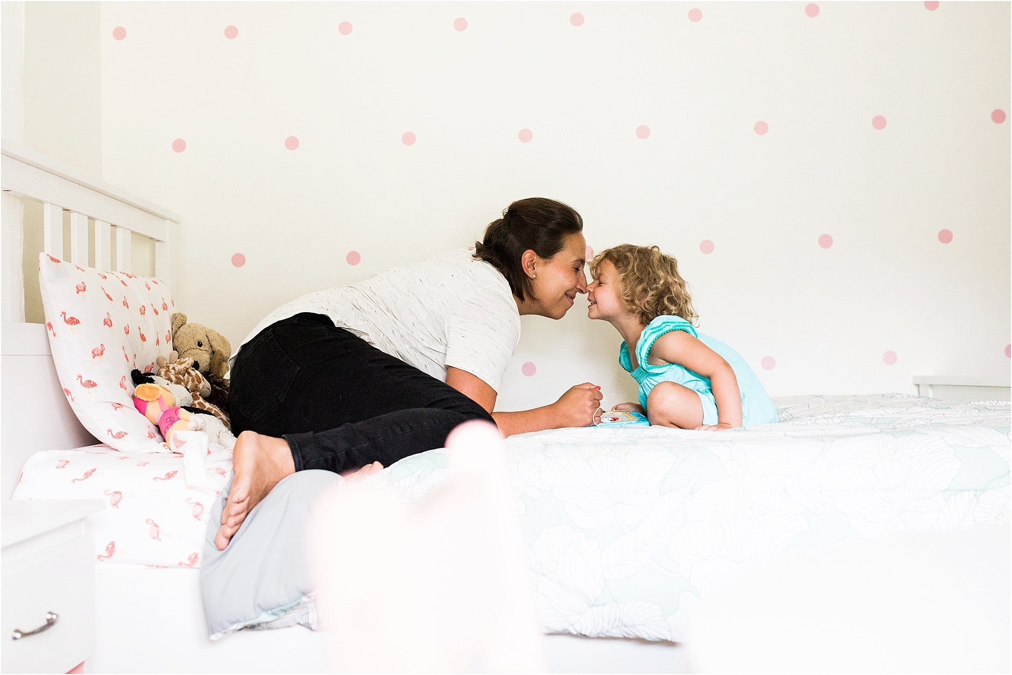 mother and daughter playing in bedroom