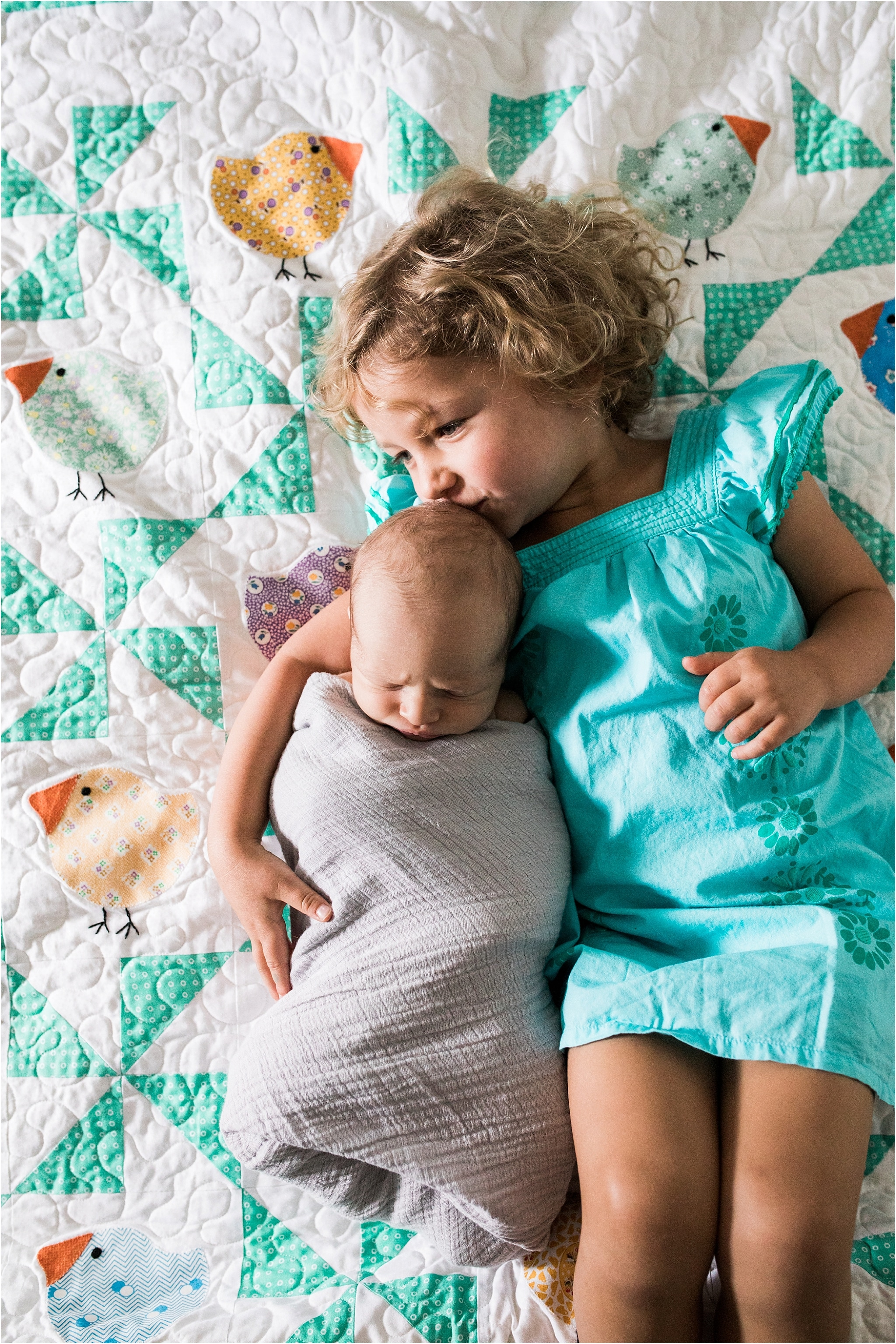 photo of big sister and new baby brother on family quilt