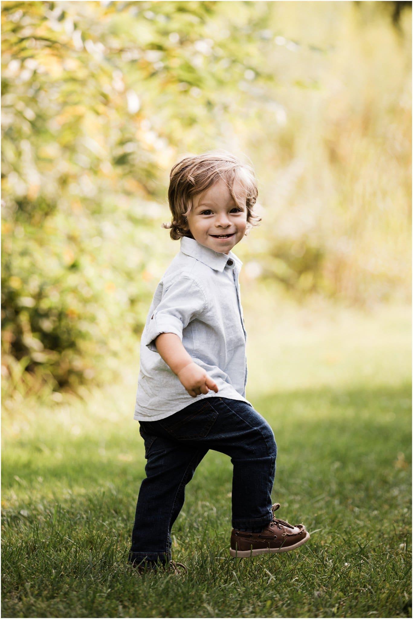 toddler boy running away smiling