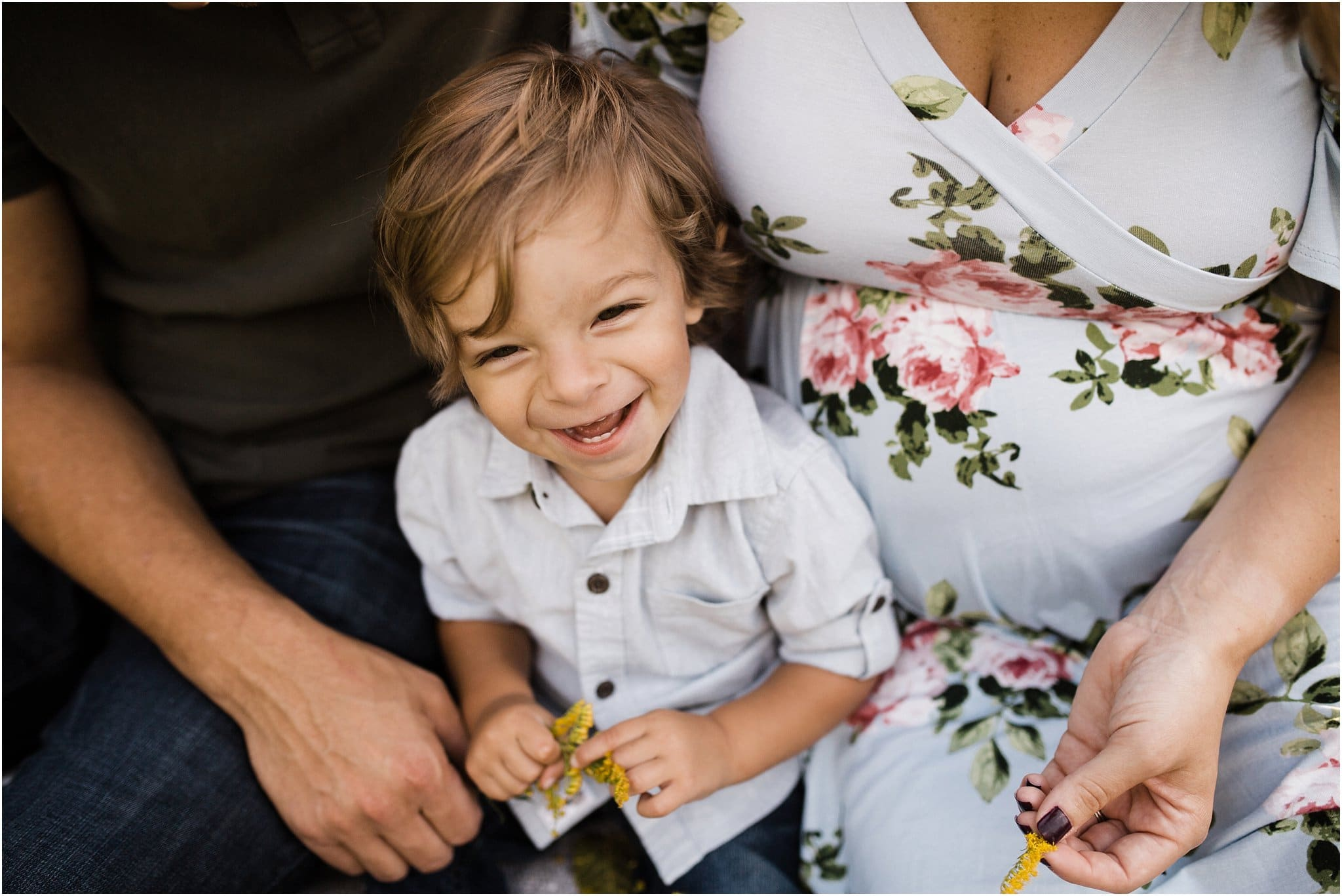 toddler boy laughing and sitting with parents