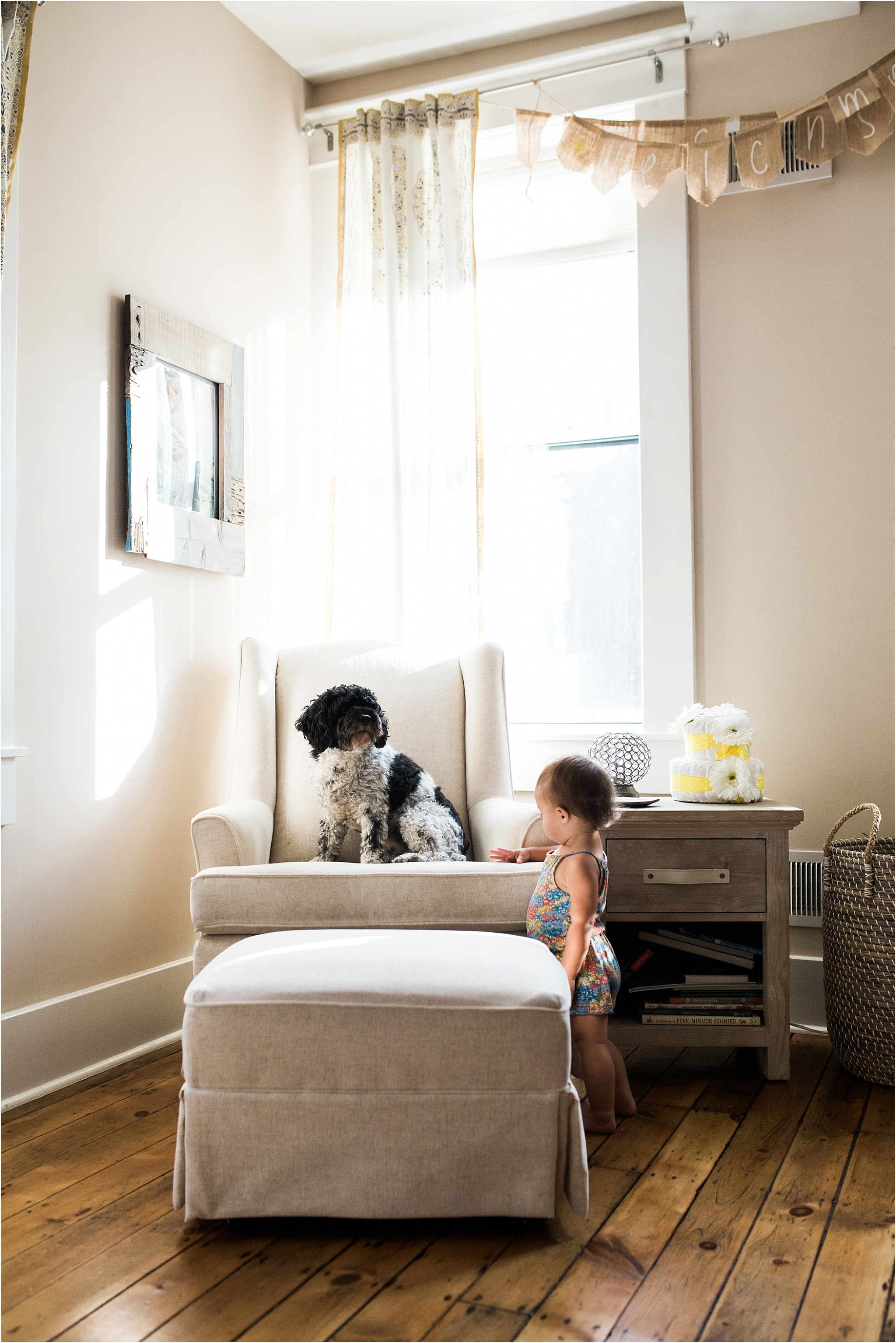 baby girl and family dog in nursery