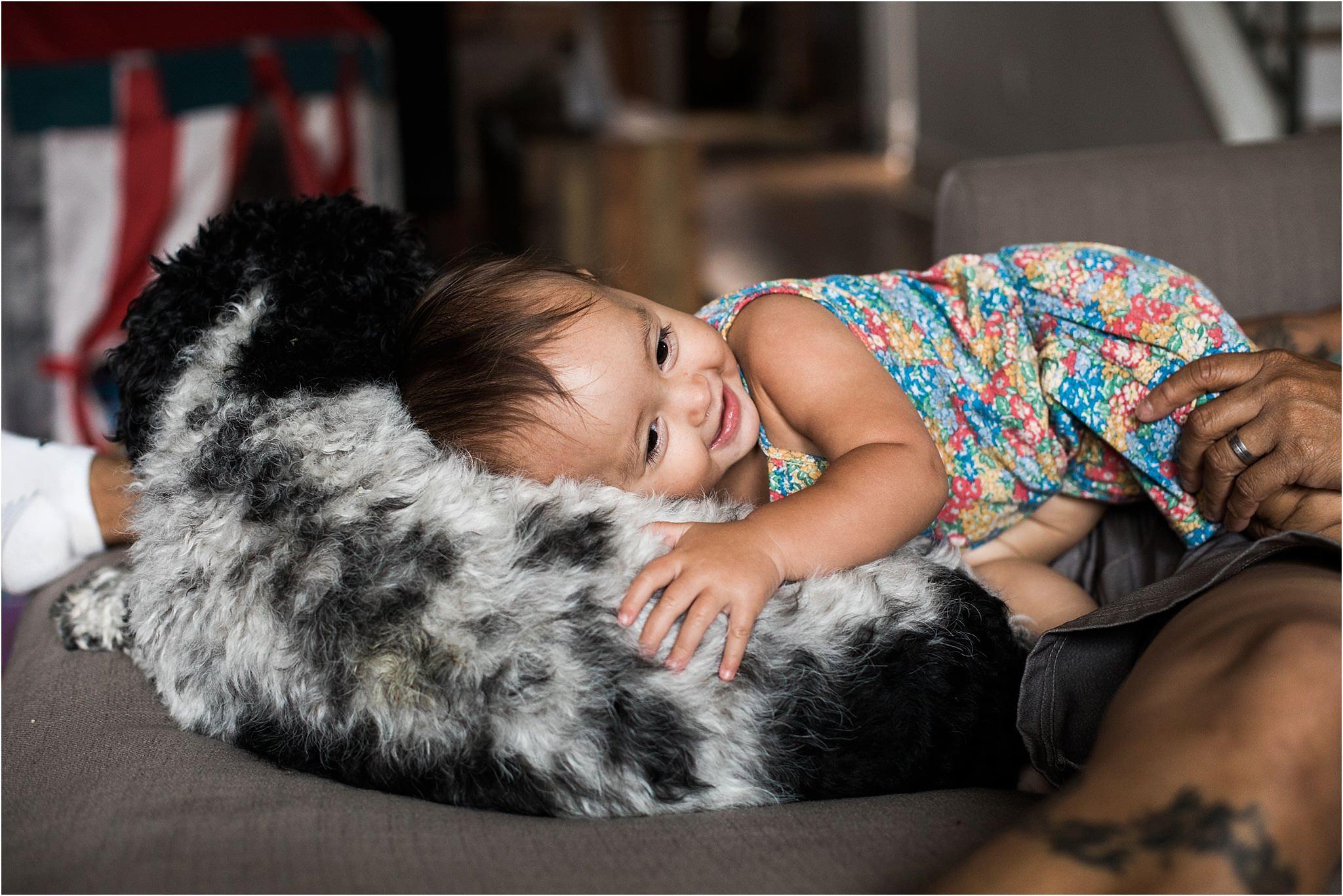 baby girl snuggling family dog on coush