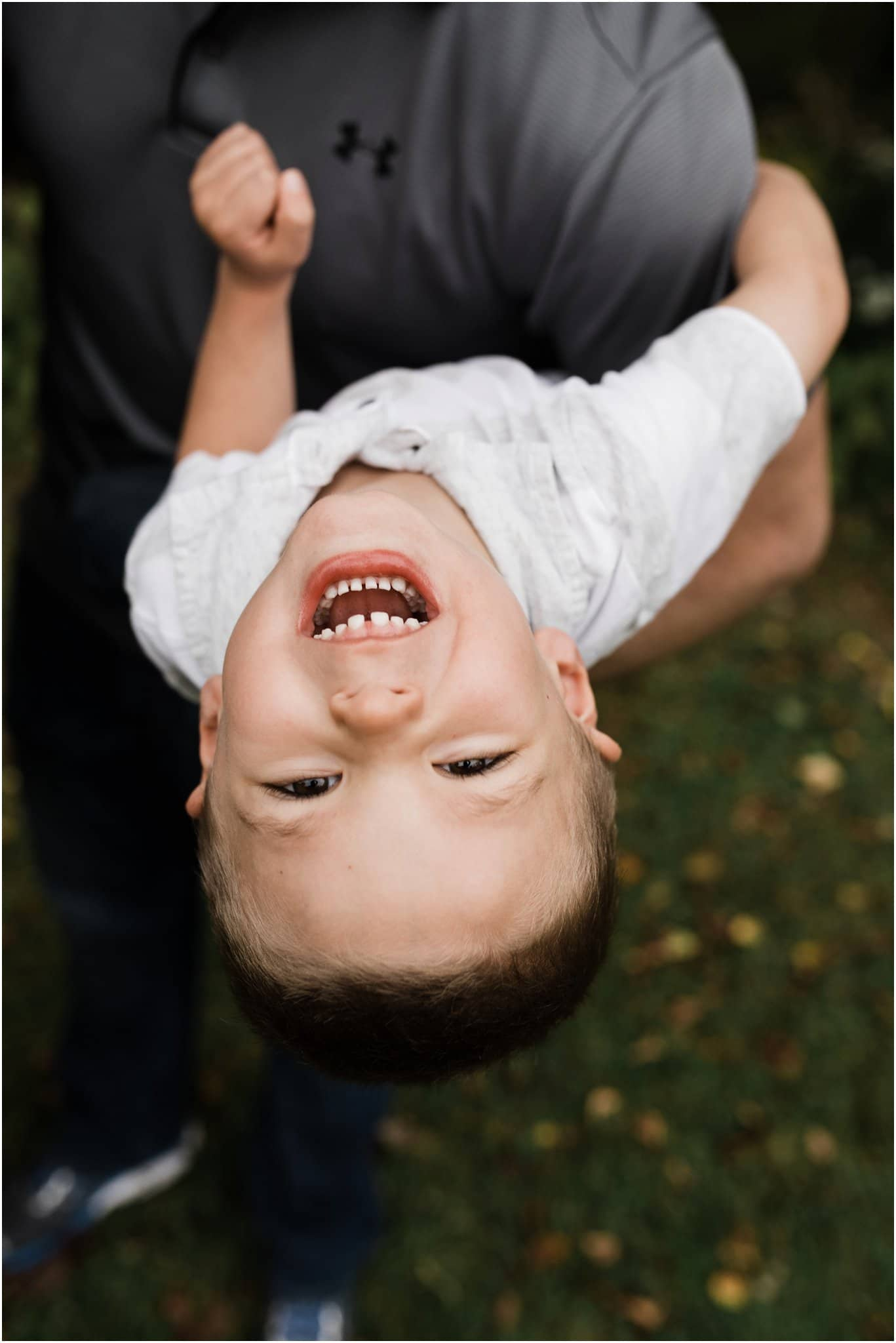 toddler boy swinging upside down from fathers arms