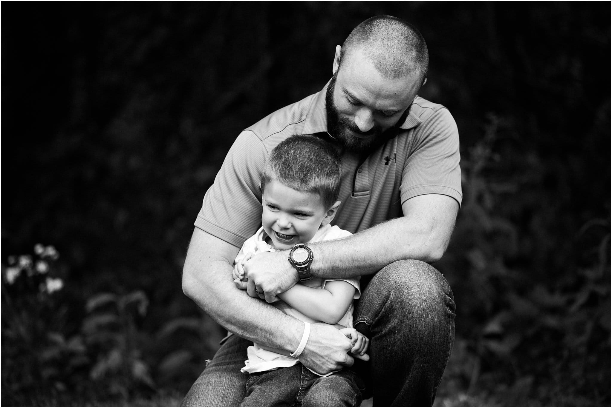 father hugging son tight and laughing