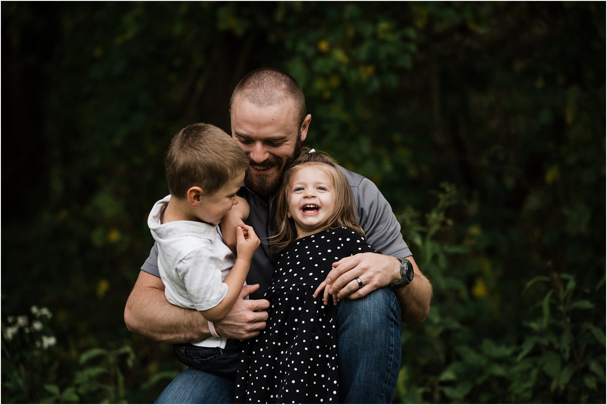 father laughing and holding children
