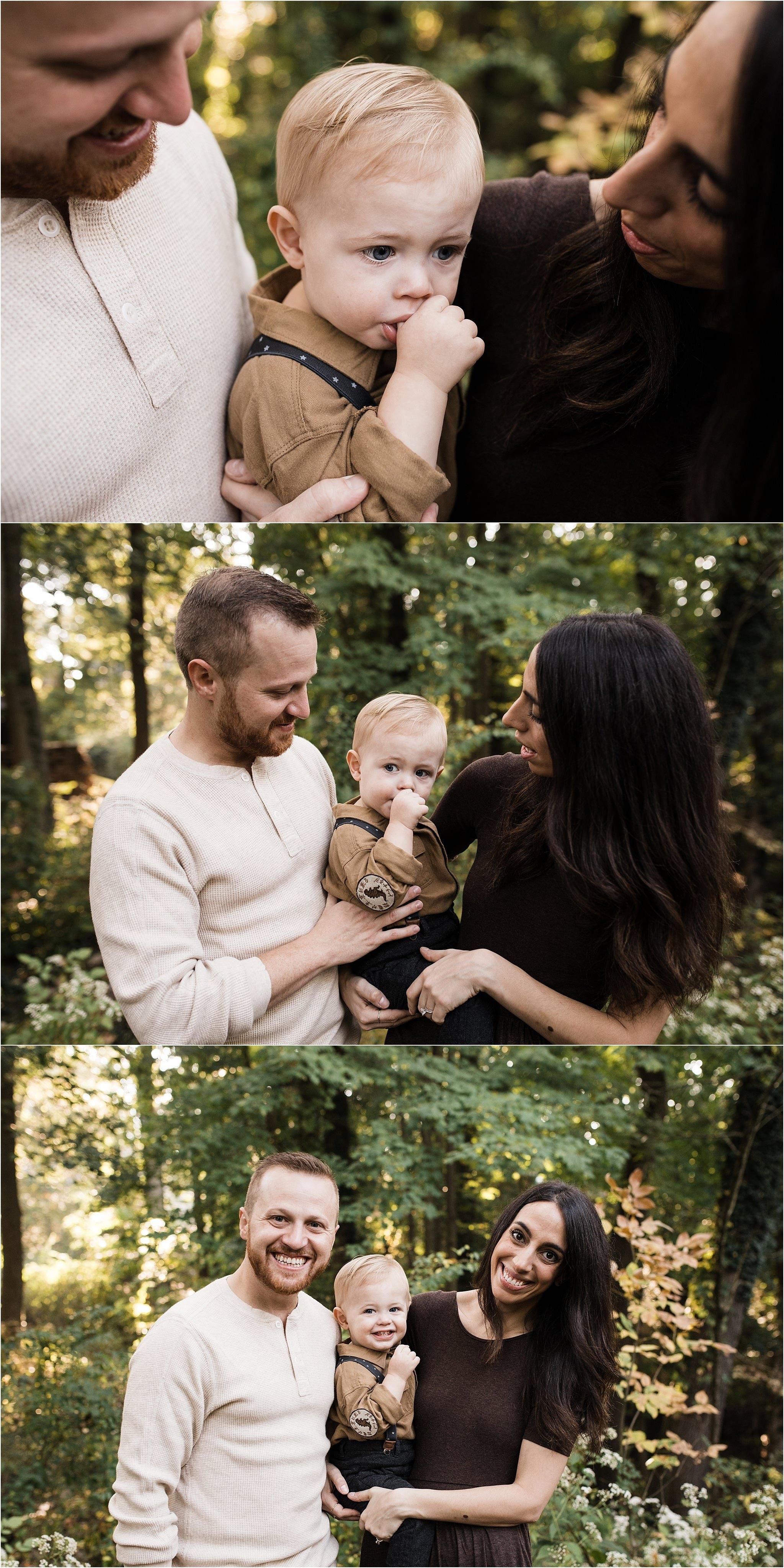 parents holding thumb sucking toddler boy