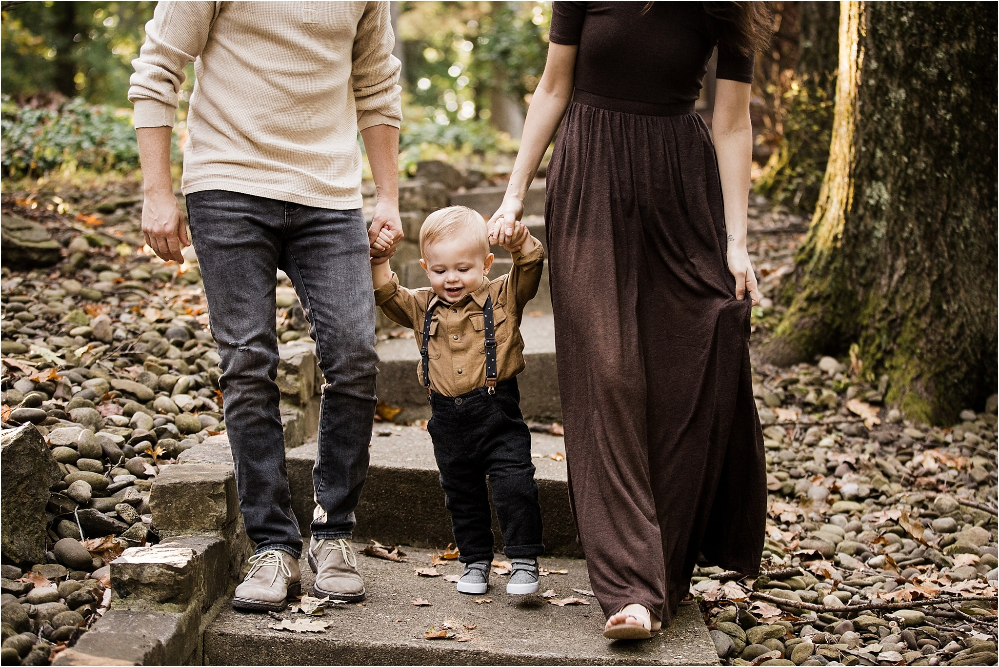 one year old boy walking holding parents hands