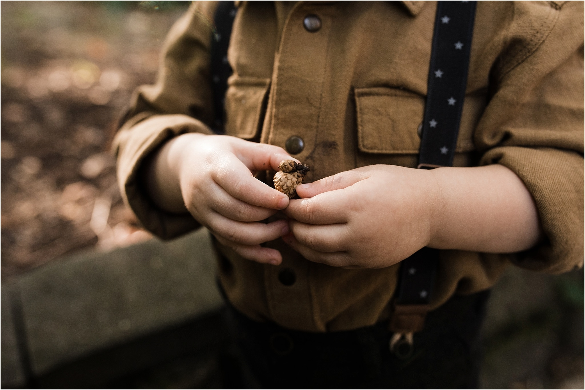 one year old boy holding acorn