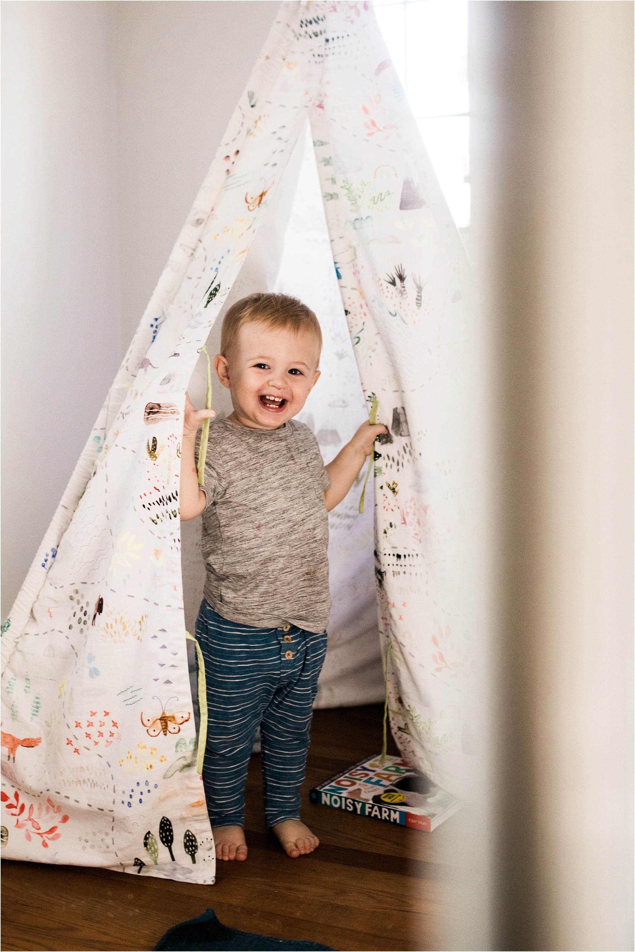 one year old boy playing in teepee