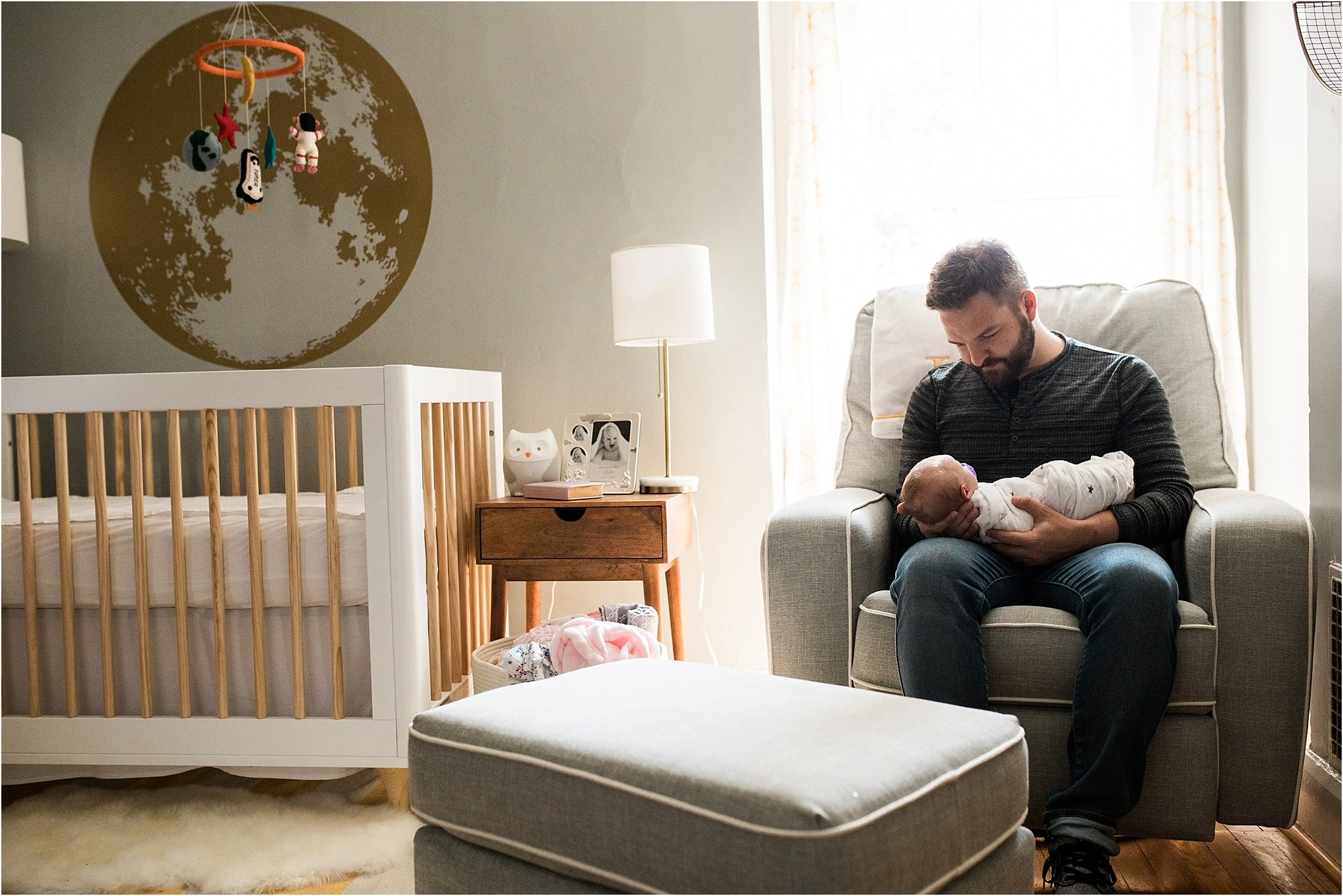 father holding newborn baby girl in home nursery