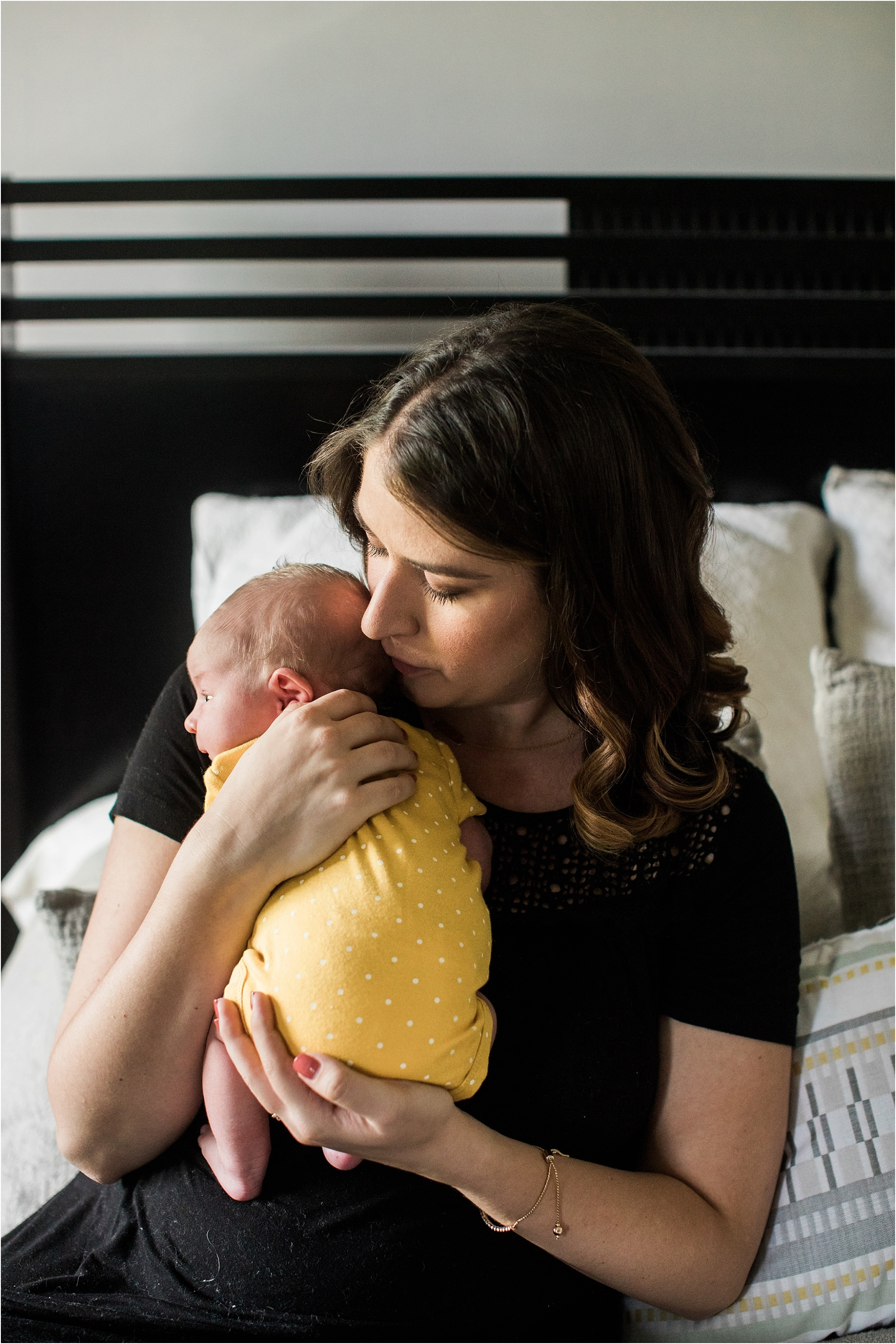 mother holding newborn baby girl in yellow onesie