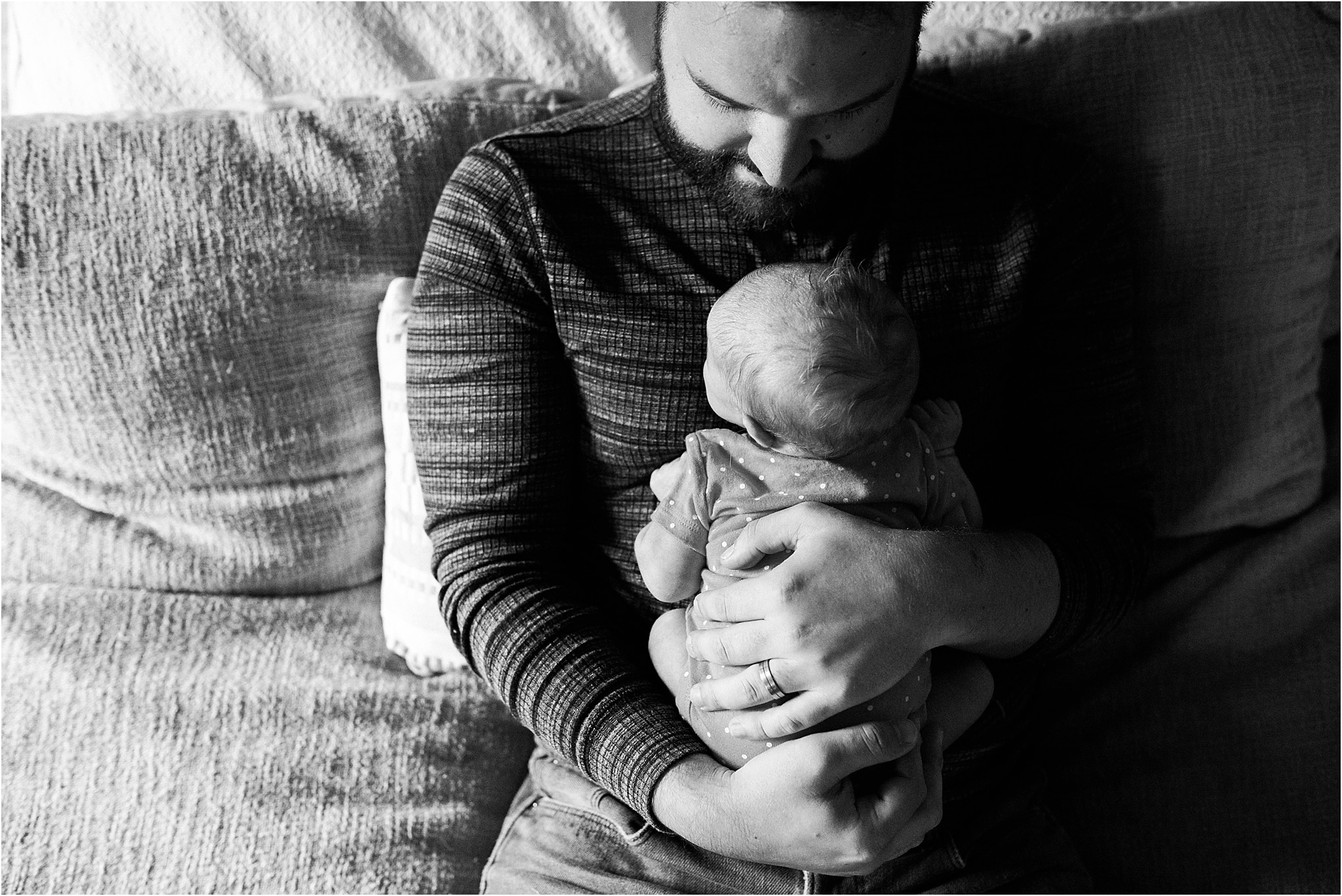 father father cuddling newborn baby in his arms