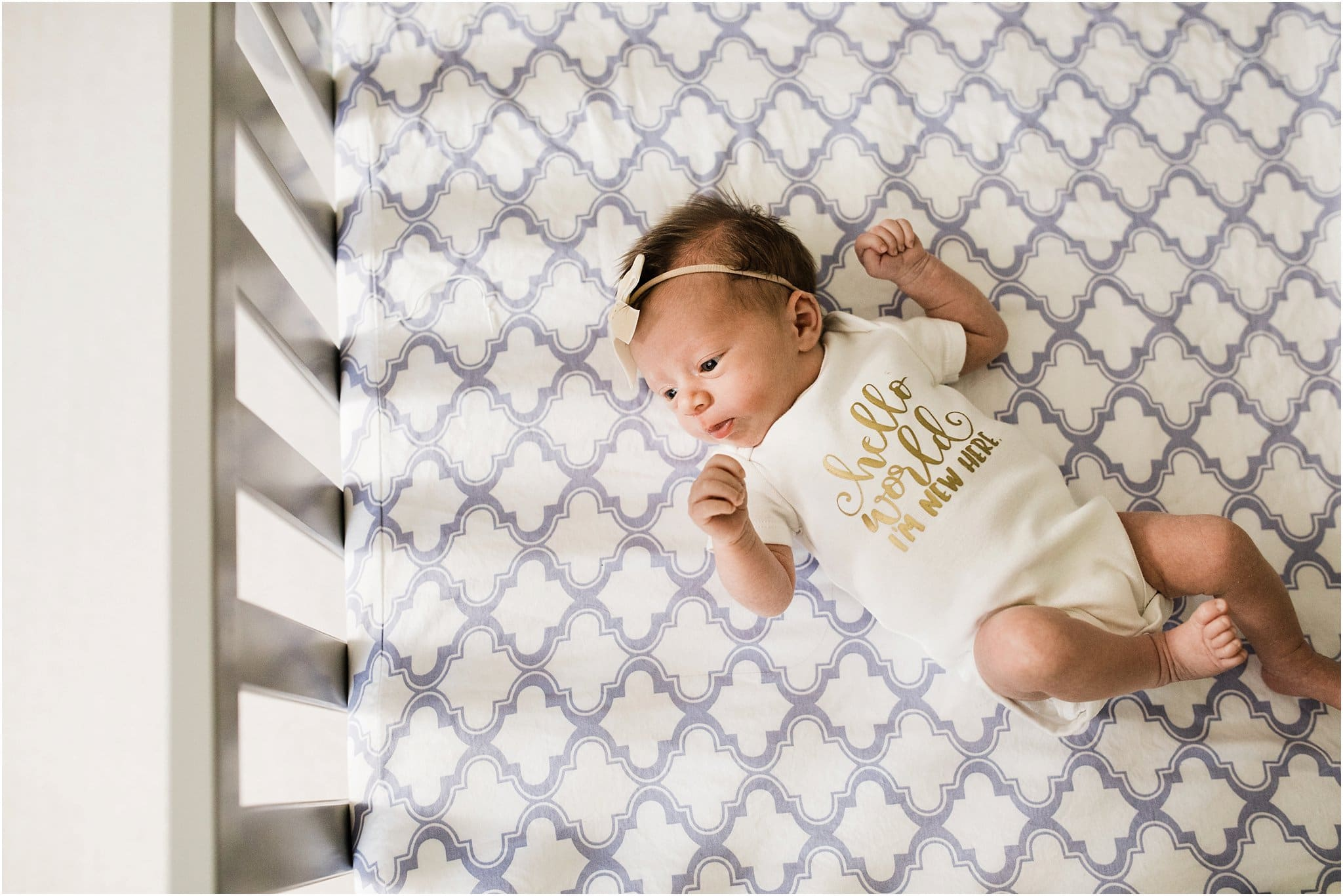 photo of newborn in crib wearing hello world I'm new here onesie