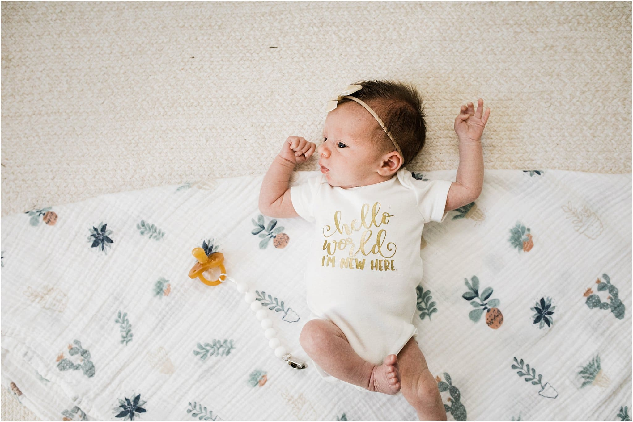 newborn baby girl laying on floral swaddle wearing i'm new here onesie