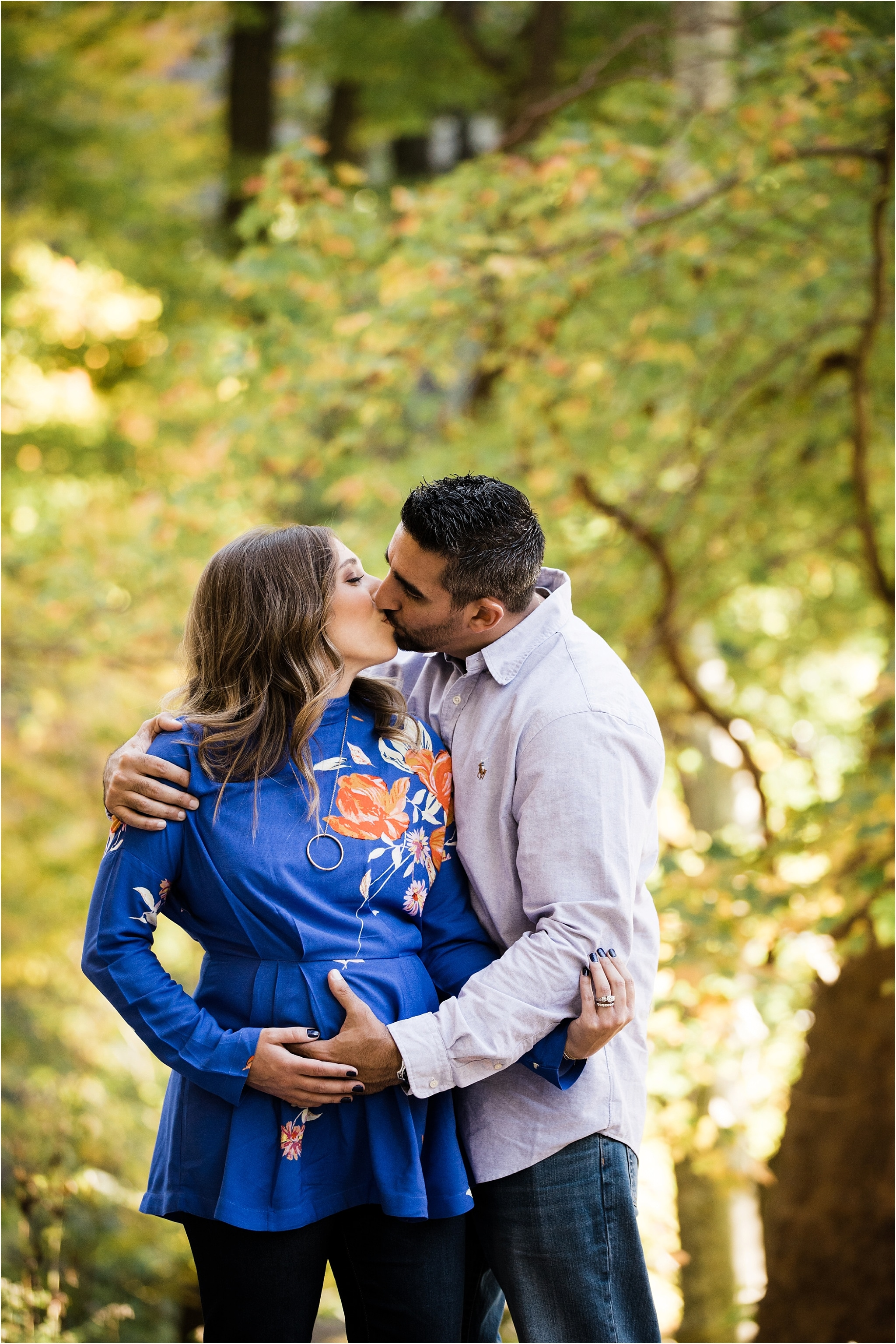 Fall maternity photos of happy couple in Schenley Park