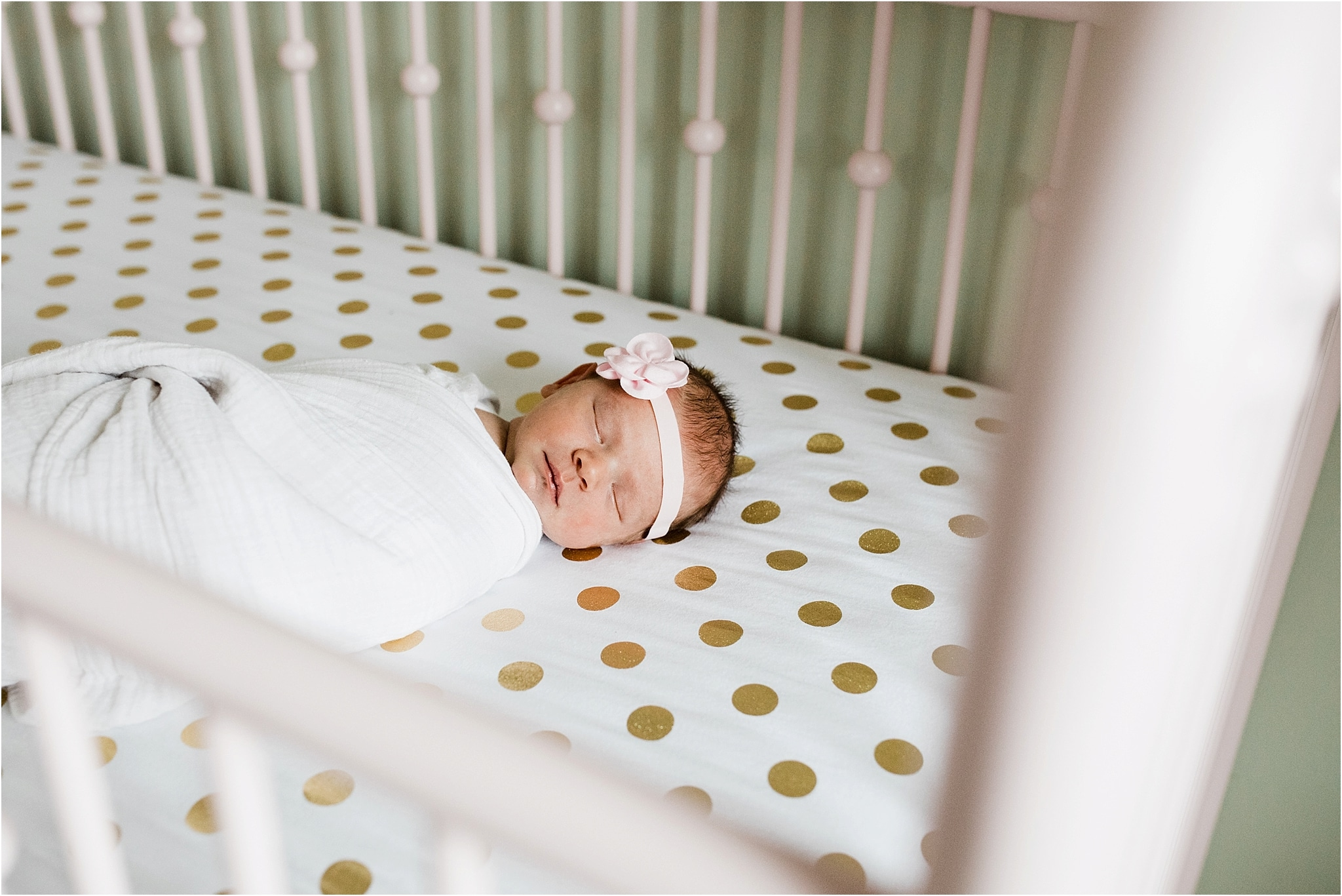newborn sleeping in pink crib with gold polka dot sheets