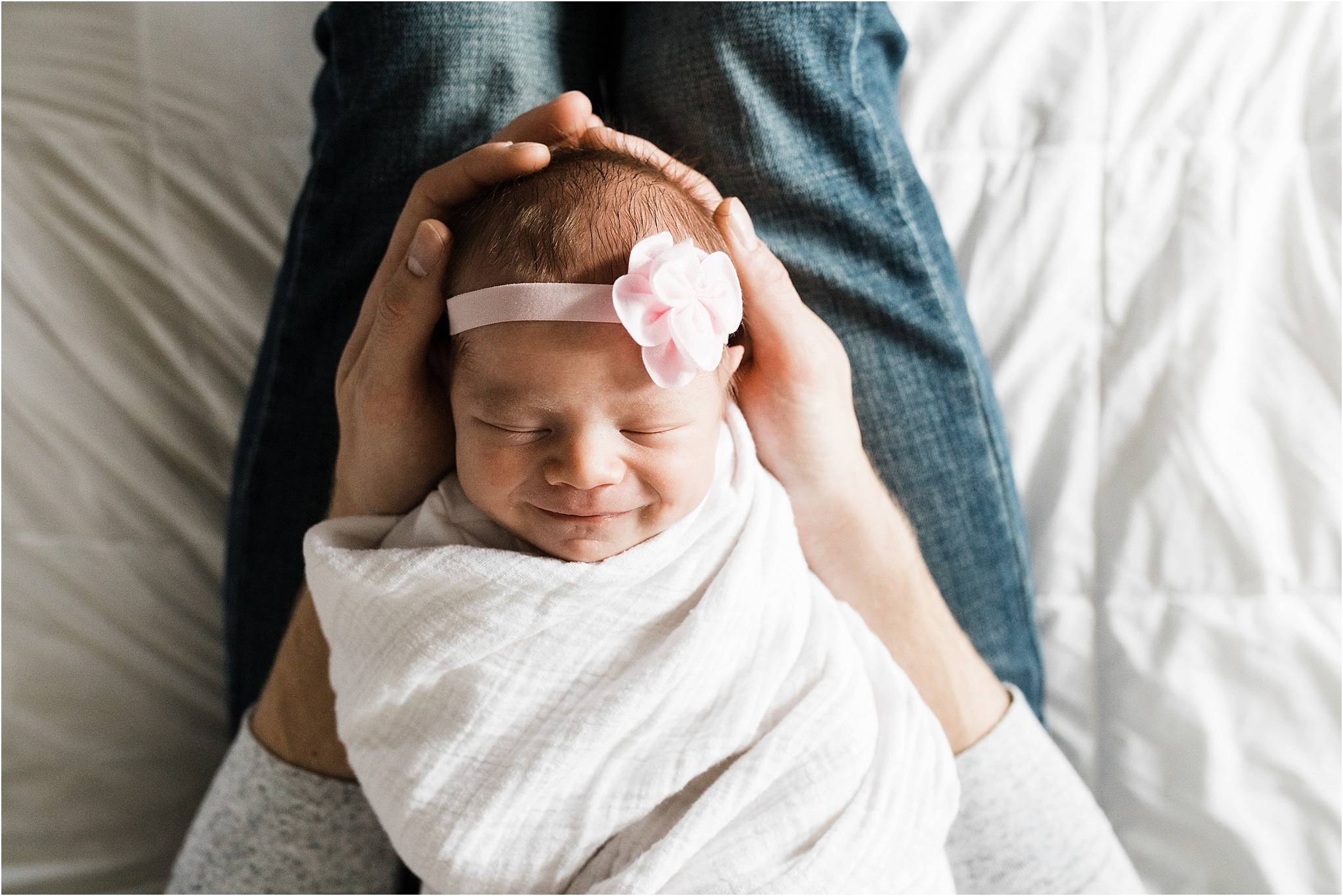 smiling newborn baby girl in daddys arms