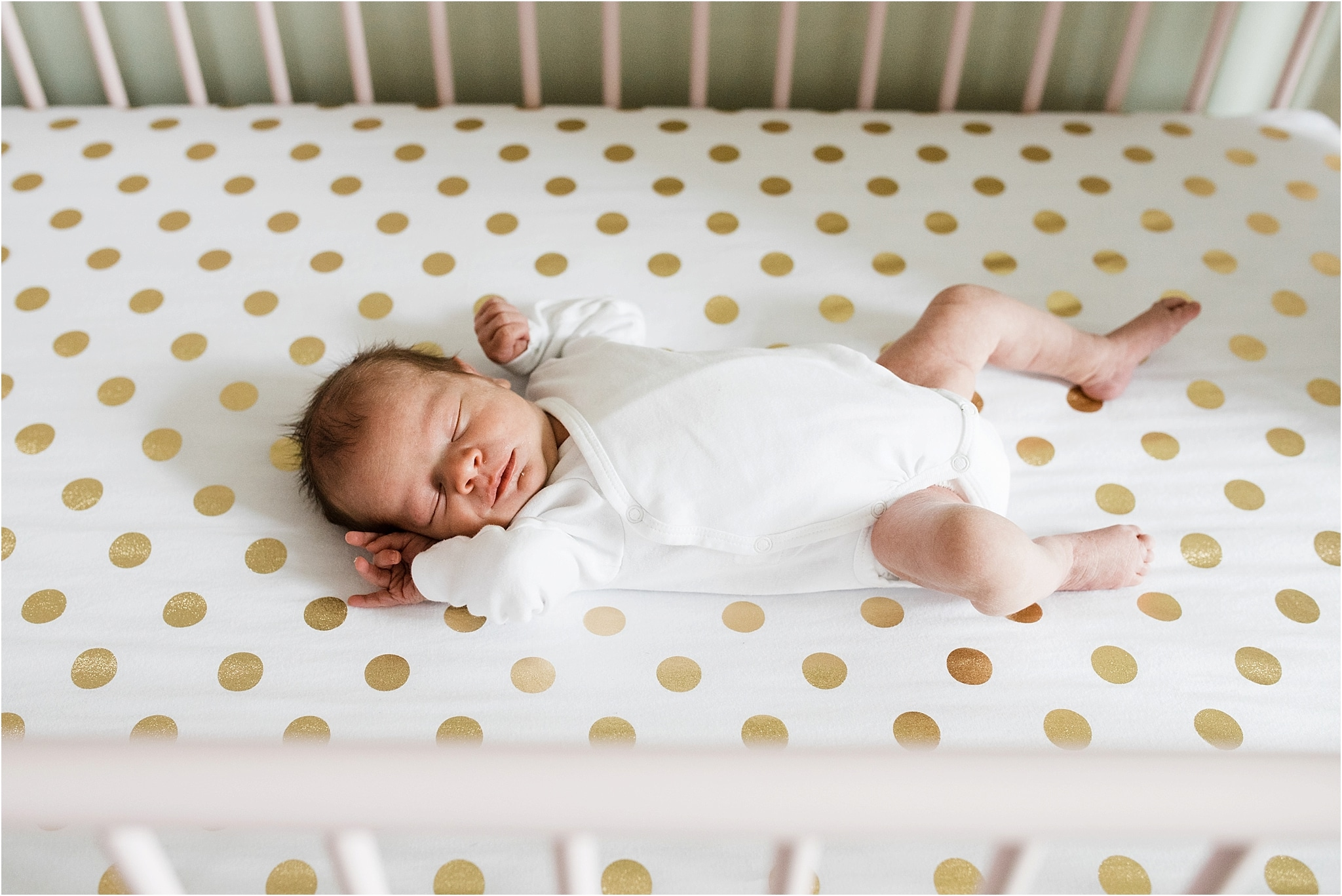 newborn in simple white onesie in crib