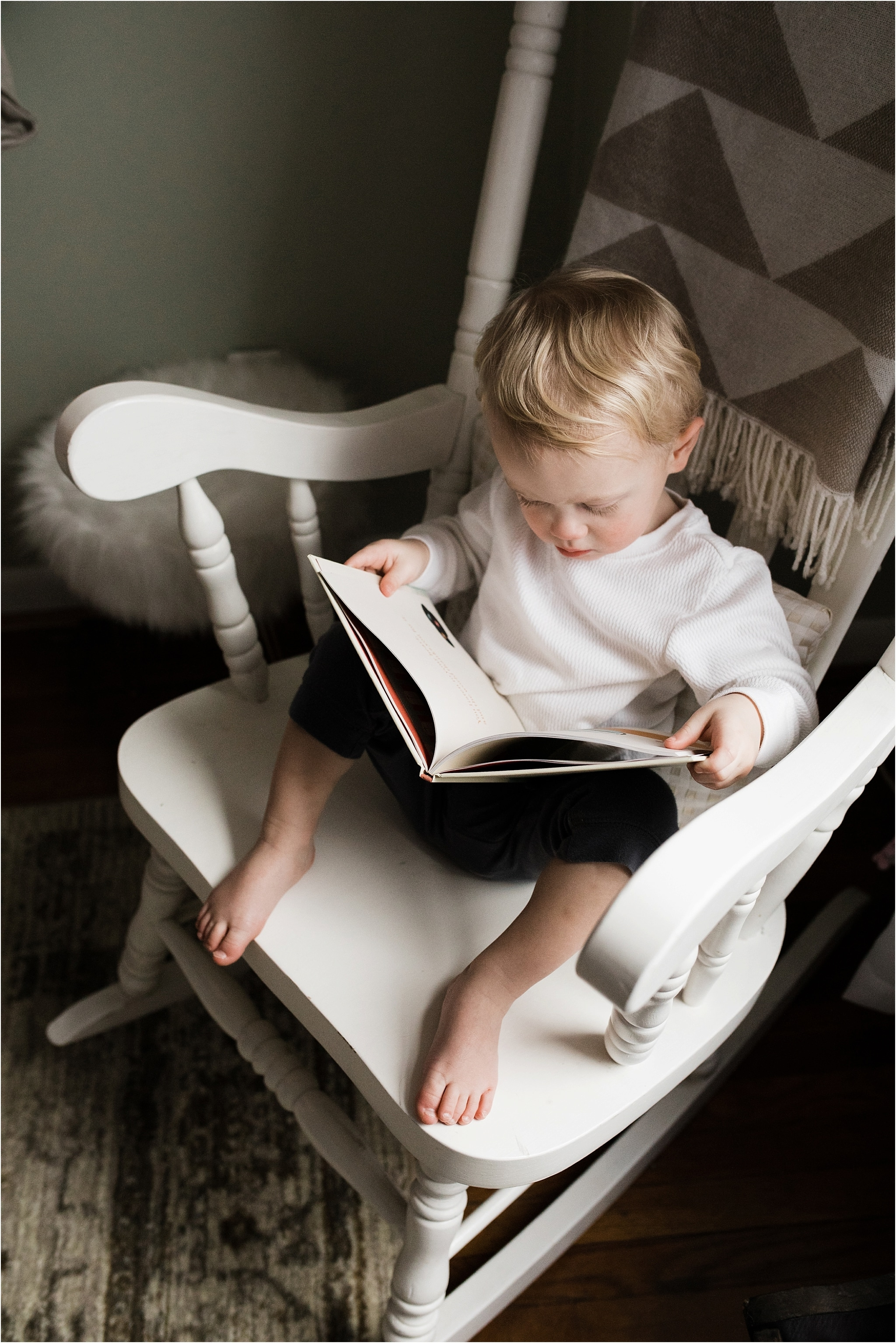 toddler boy reading in sisters nursery