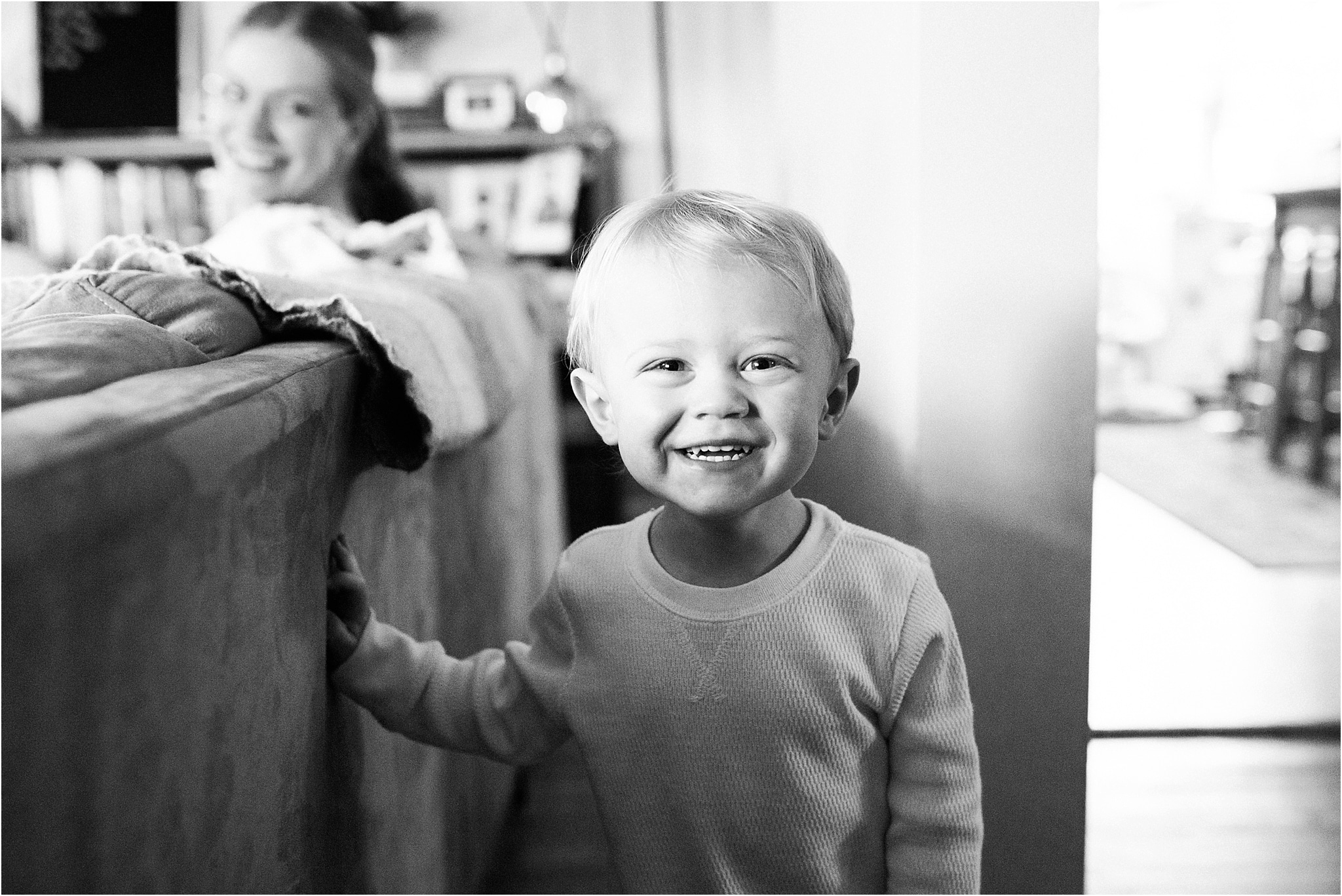 big brother smiling during family newborn session at home