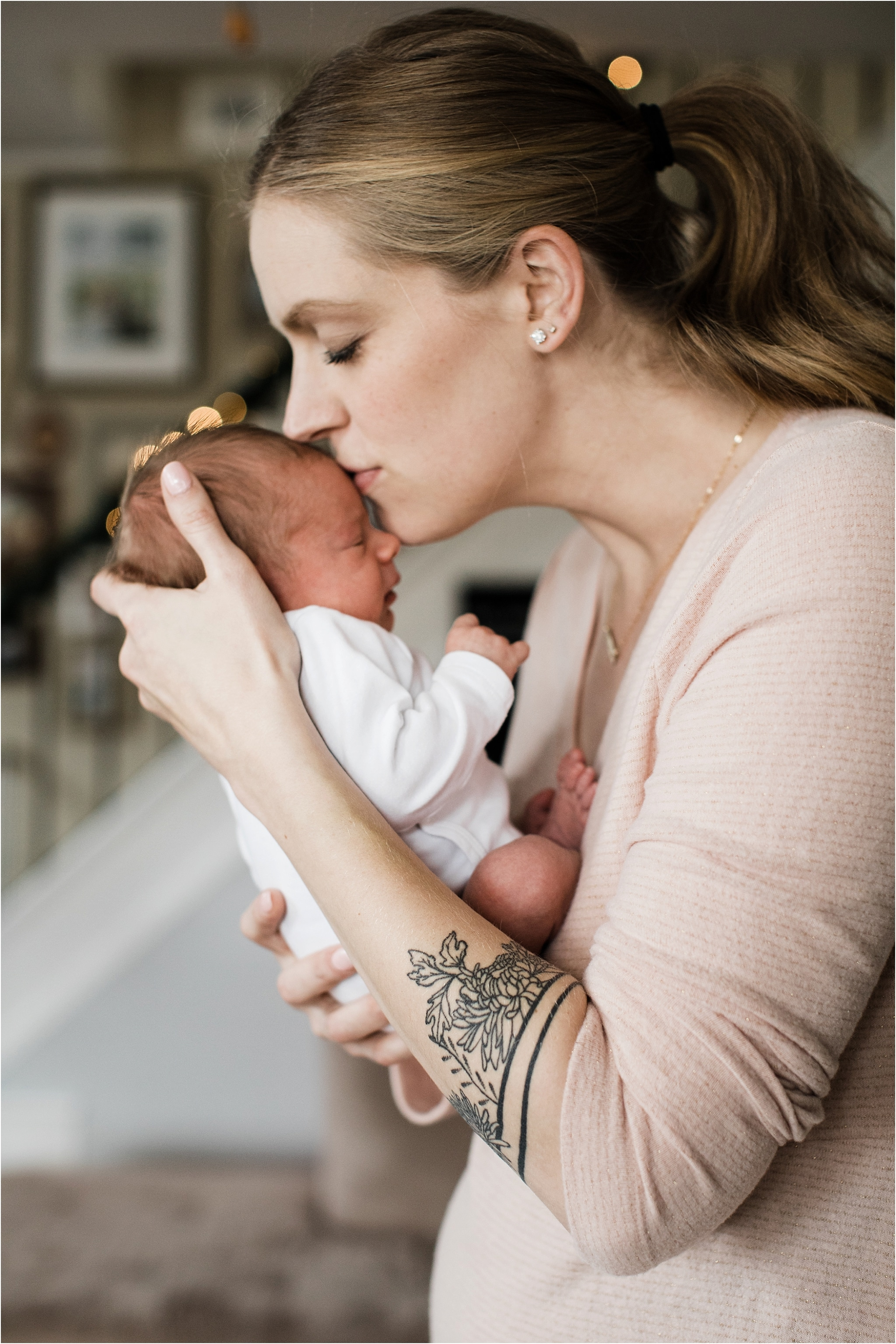 mother with meaningful tattoo kissing her rainbow baby
