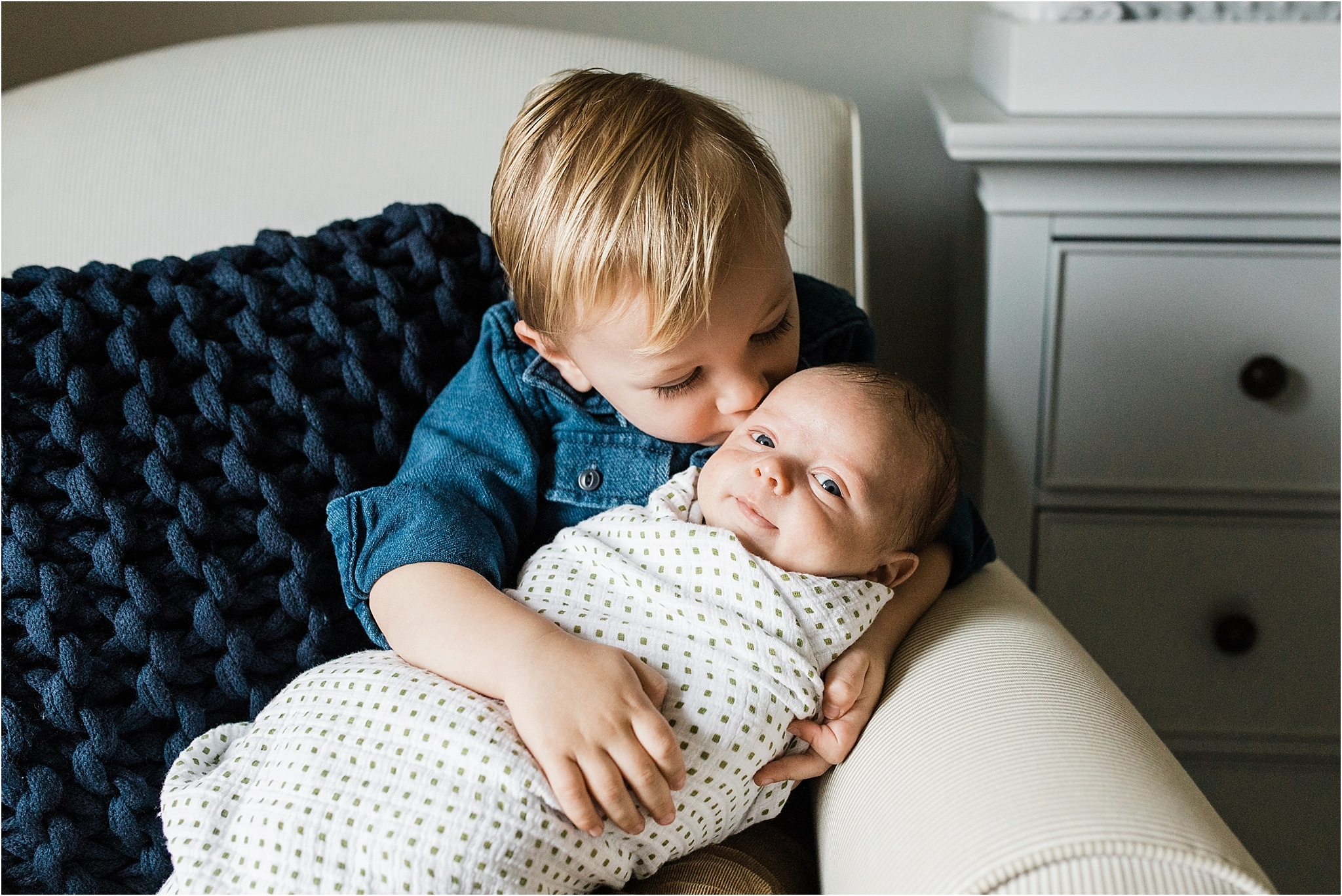 big brother holding and kissing new baby brother in home nursery