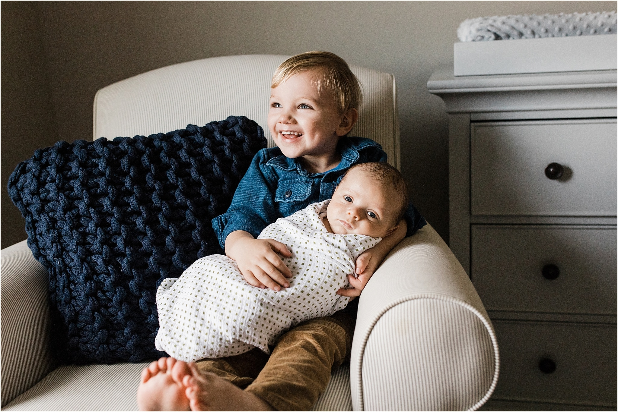 big brother holding and loving new baby brother in home nursery