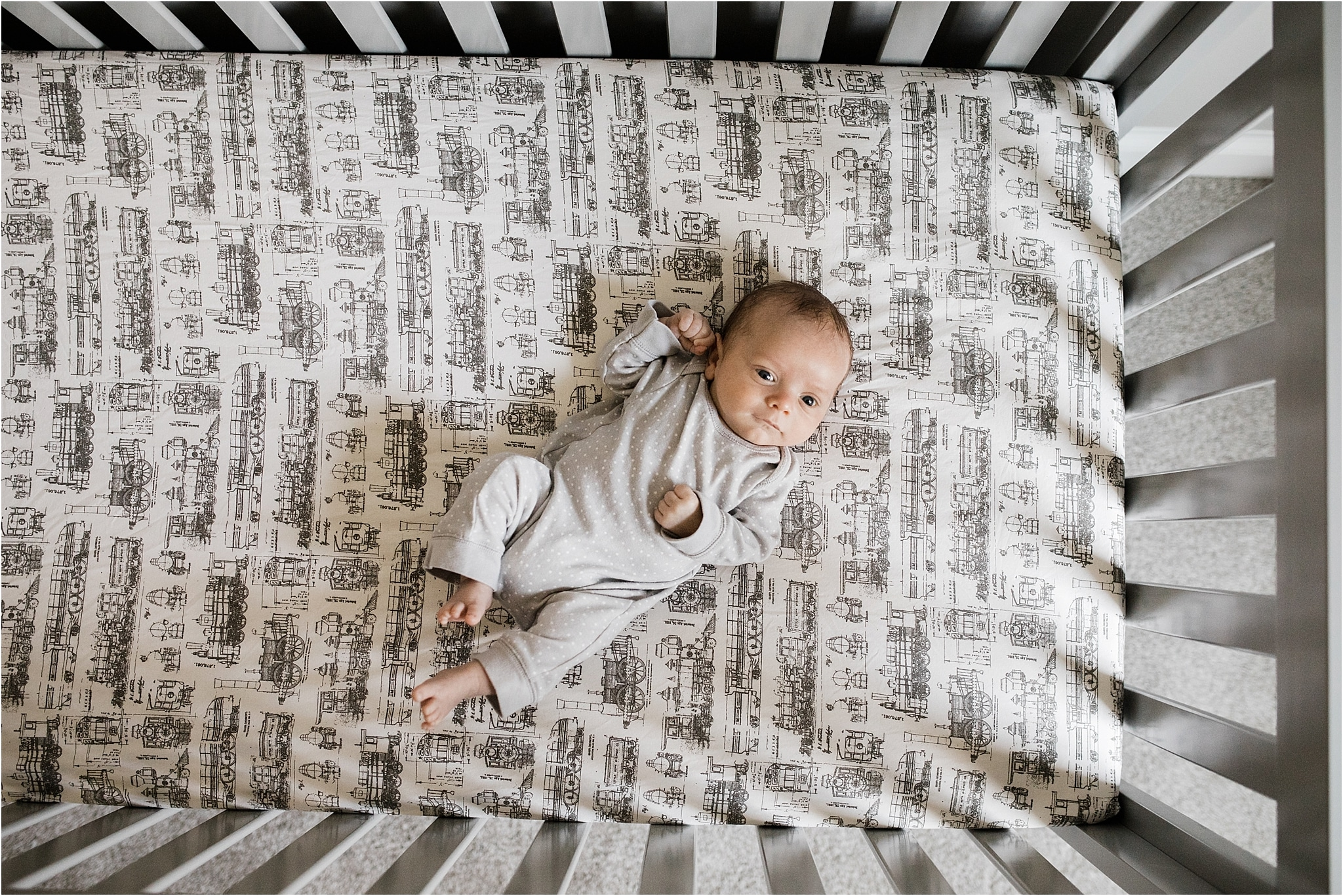 newborn baby boy in crib with train sheets