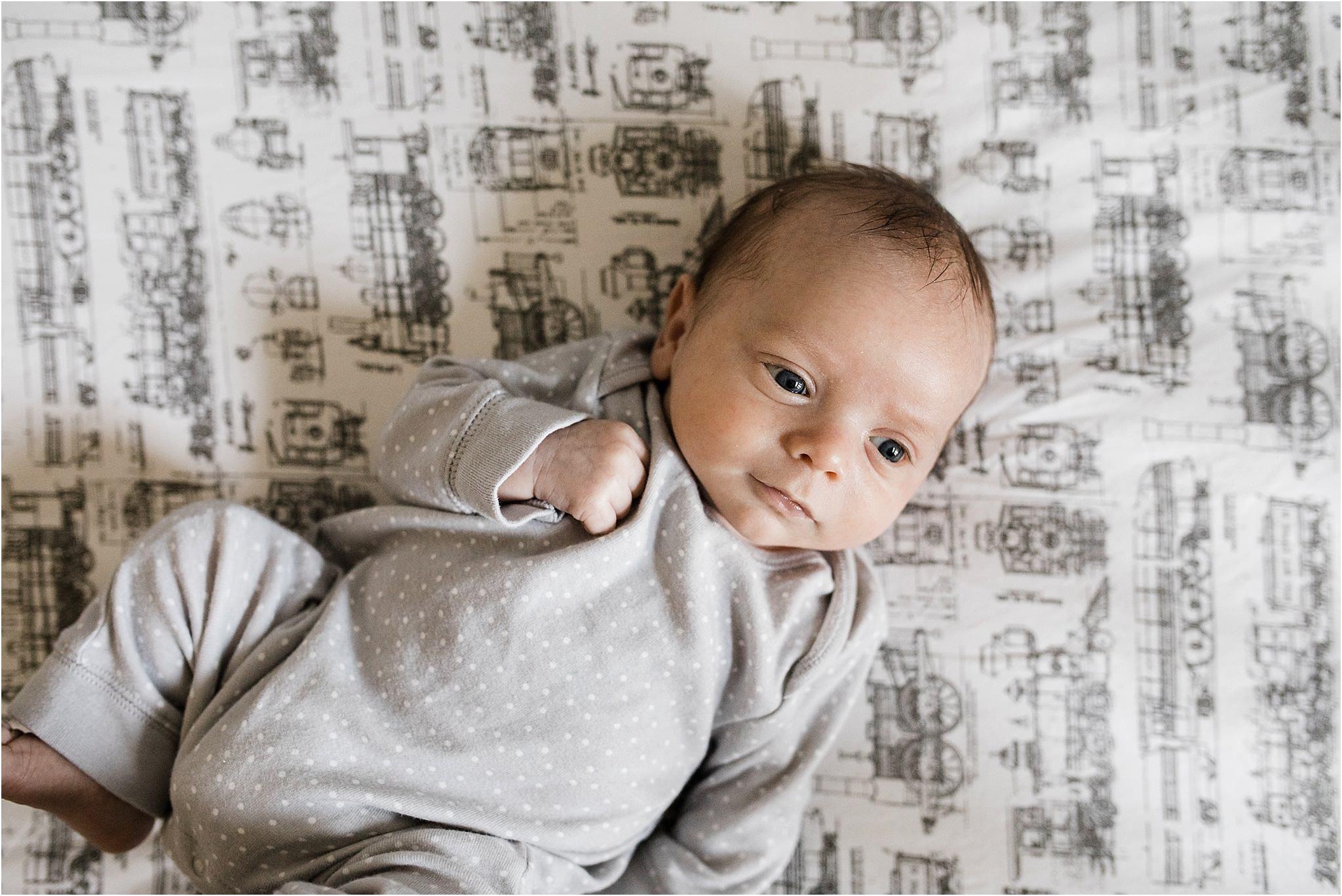 newborn baby boy in crib with train sheets